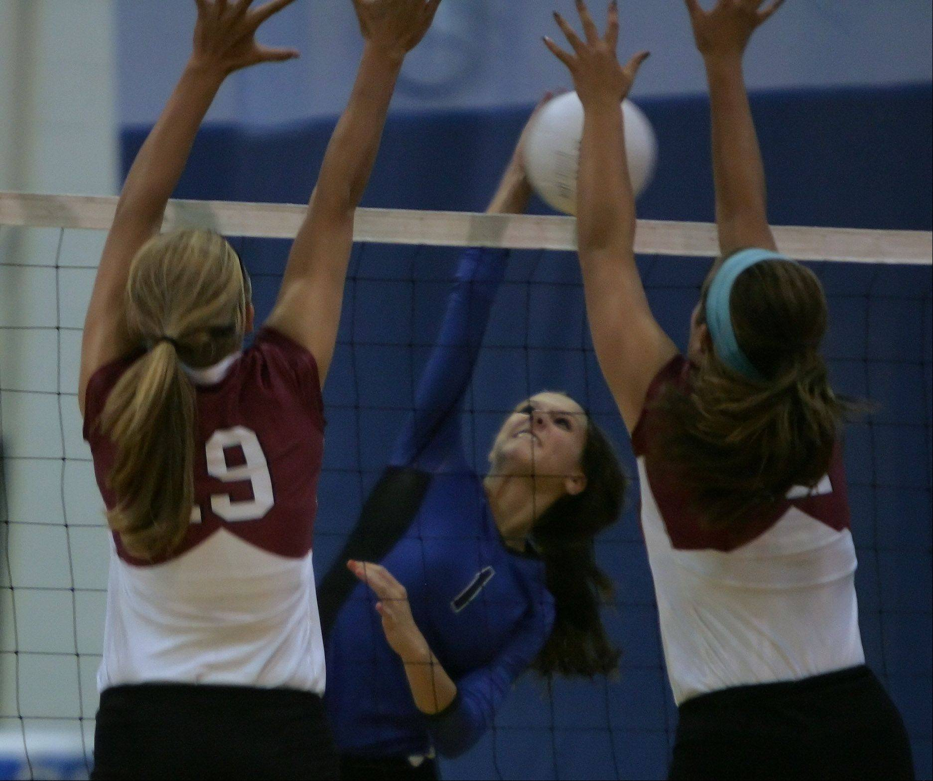 Lake Zurich's Mickenzie Andrews slams the ball past two Prairie Ridge blockers on Tuesday.