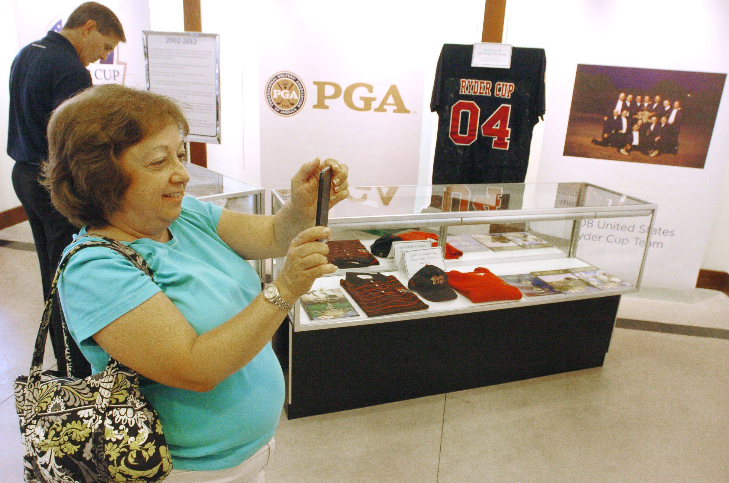 Mary Ann Bolster of Villa Park makes a picture of memorabilia on display.