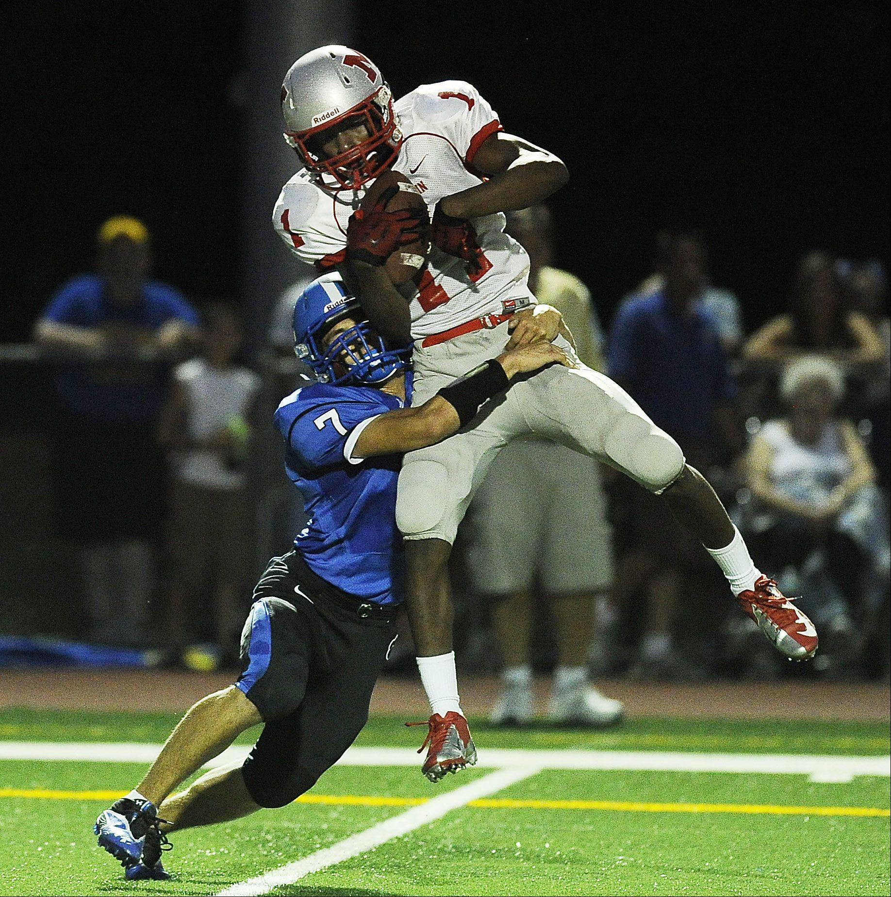 Mundelein's Chance Lindsey hauls in a pass despite pressure from Wheeling's Michael Yoshino in the season opener of Friday night football at Wheeling High School.