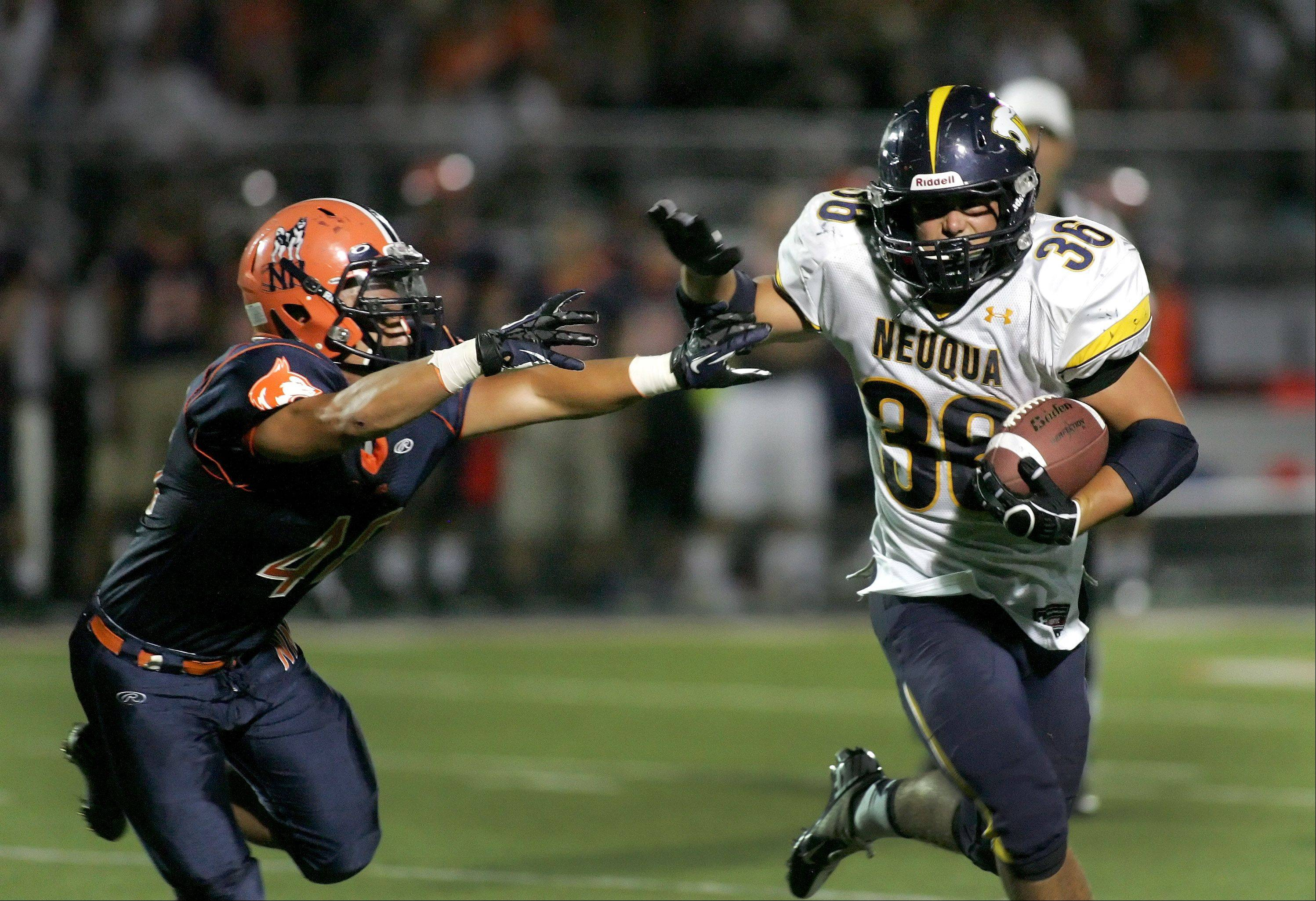 Neuqua Valley's Joey Rhattigan, right, holds off Naperville North's Eric Montgomery in football action Friday in Naperville.