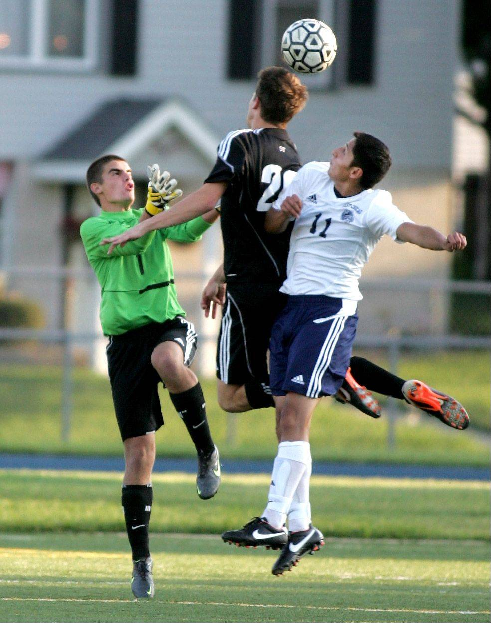 Marshall West of Wheaton Academy, center, gets sandwiched between West Chicago goalkeeper Paolino Mansera, left, and Steven Porcayo in boys soccer action Tuesday.