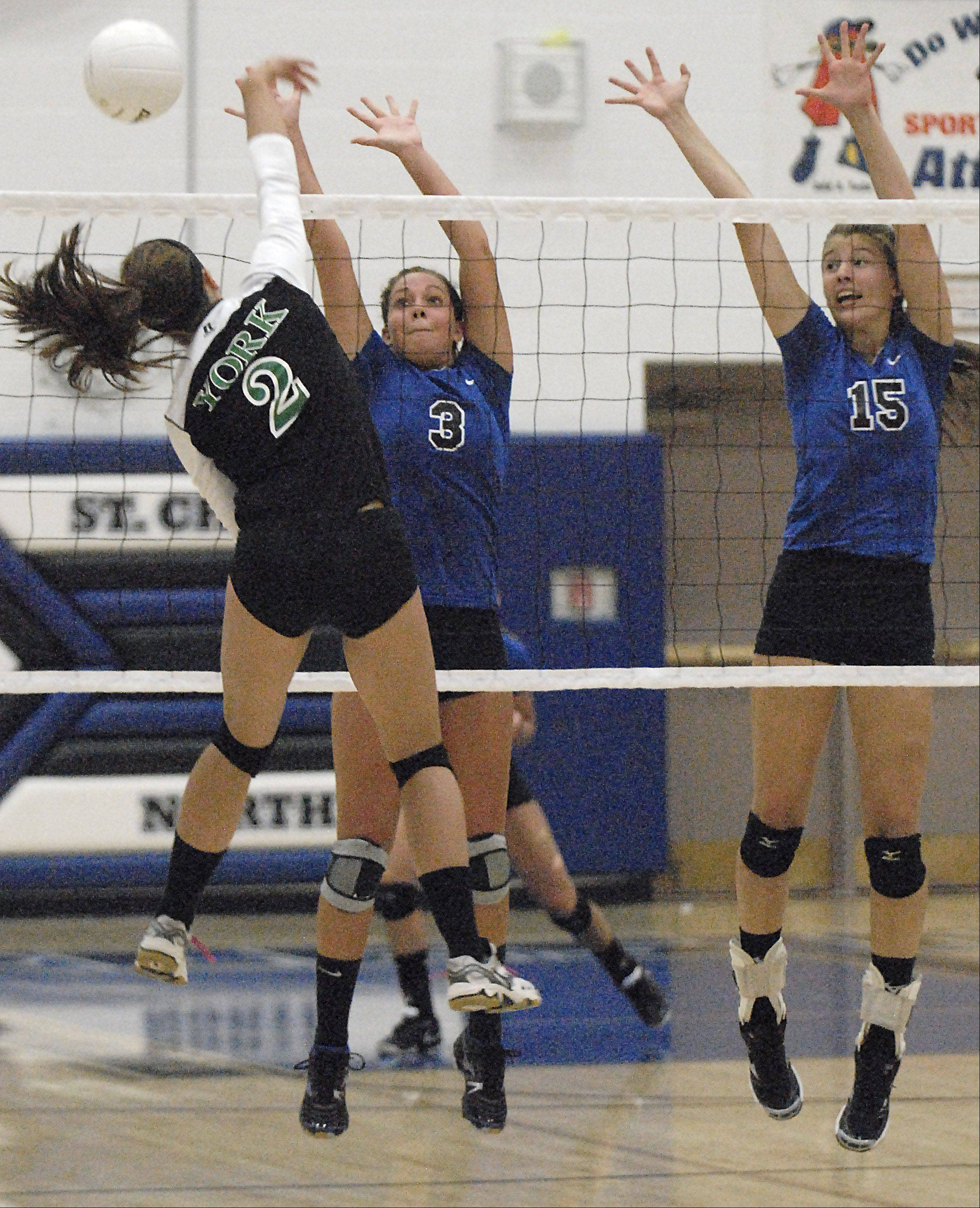 St. Charles North's Emily Belz and Alex Stone attempt a block on a spike by York's Alexandra Preuss in game three on Tuesday.