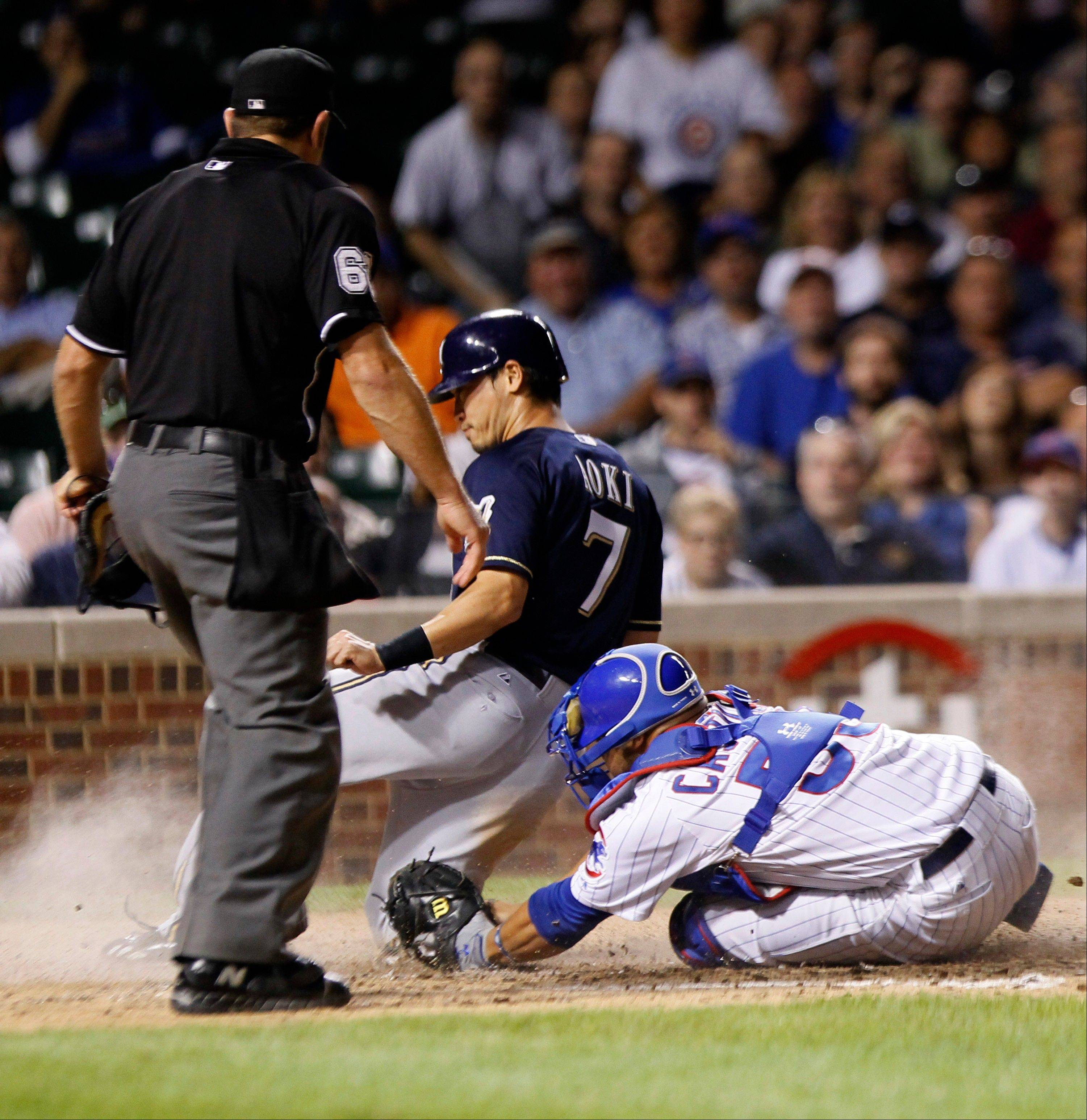 Milwaukee's Norichika Aoki scores past Cubs catcher Steve Clevenger after Rickie Weeks was caught in a rundown trying to steal second during the eighth inning Tuesday at Wrigley Field.