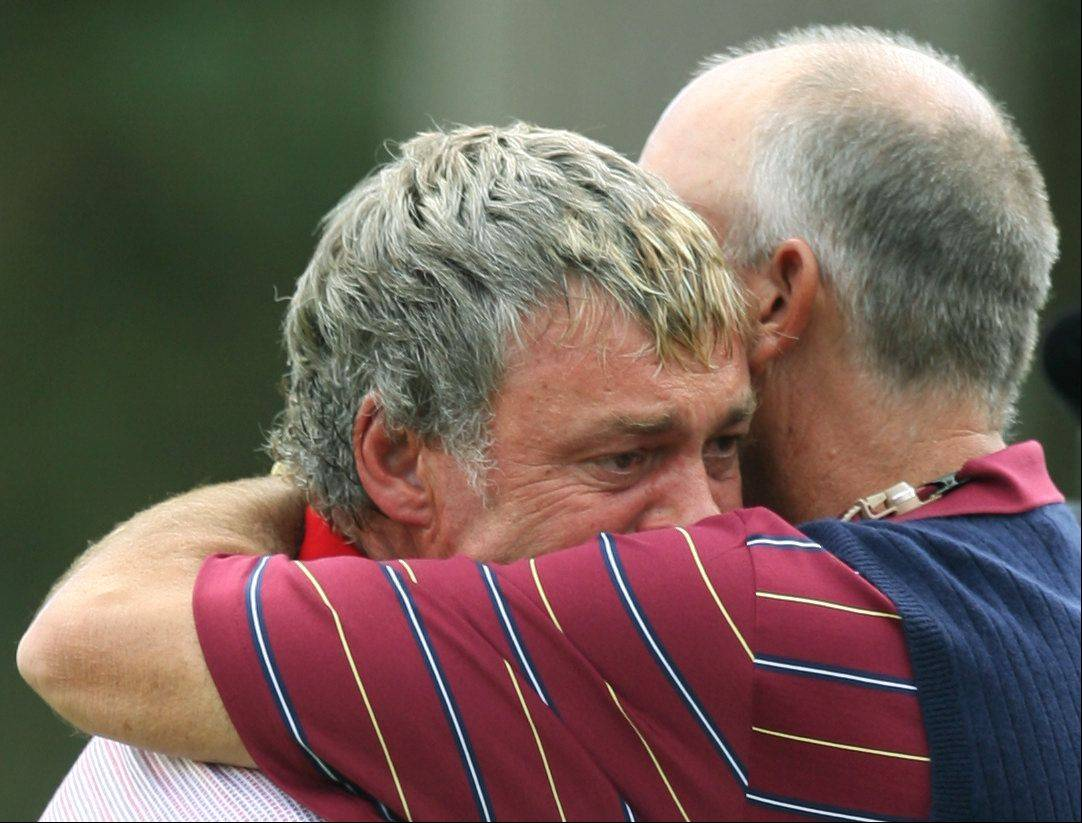 Europe's Darren Clarke, left, is hugged by United States team captain Tom Lehman on the 16th green after Clarke won his singles match against Zach Johnson of the United States on the last day of the 2006 Ryder Cup at the K Club golf course, Straffan, Ireland, Sunday Sept. 24, 2006. Clarke won the match 3 and 2. The European team earlier retained the Ryder Cup, Clarke, hero of the 2006 Cup for the Europeans, lost his wife shortly before the 2006 Cup,