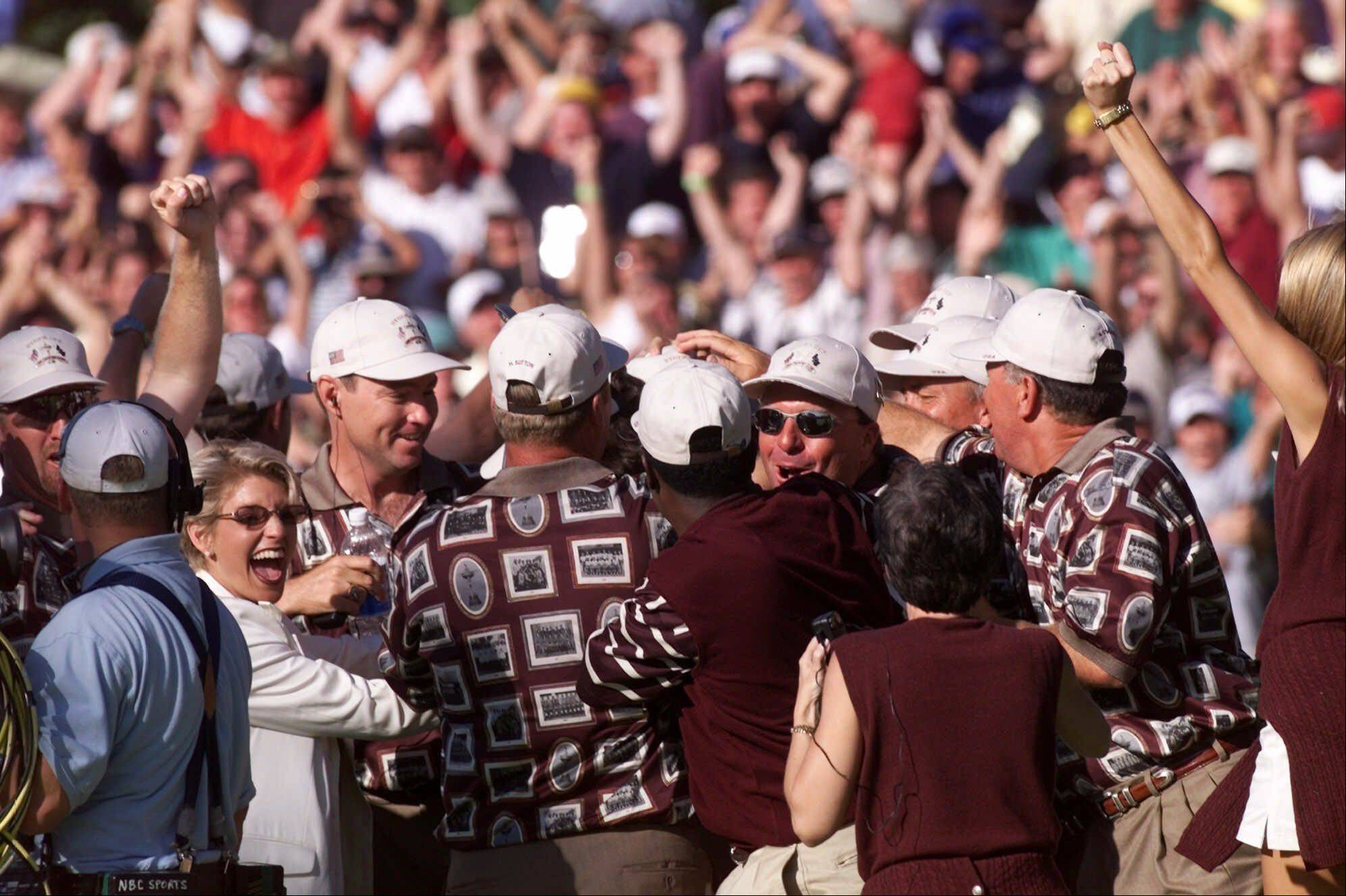 U.S. Ryder Cup players, wives, and team officials surround Justin Leonard on the 17th hole after his final round match Sunday, Sept. 26, 1999 in Brookline, Mass. The Americans were criticized for excessive celebration in reaction of their 1999 victory.