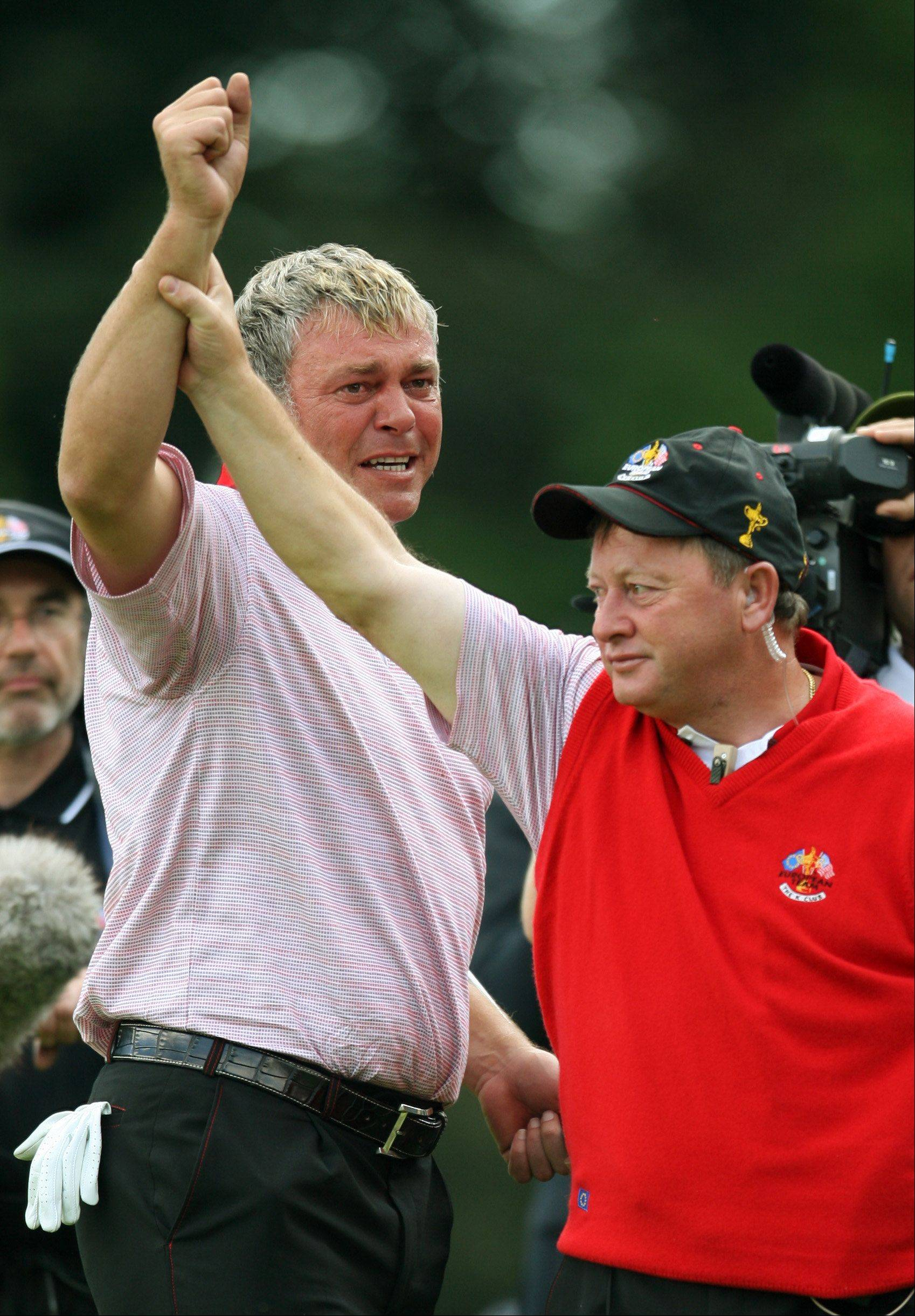 Europe's Darren Clarke's, arm is held aloft by team captain Ian Woosnam, right, on the 16th green after winning his singles match against Zach Johnson of the United States on the last day of the 2006 Ryder Cup at the K Club golf course, Straffan, Ireland, Sunday Sept. 24, 2006. Clarke won the match 3 and 2. The European team earlier retained the Ryder Cup, Clarke, hero of the 2006 Cup for the Europeans, lost his wife shortly before the 2006 Cup,