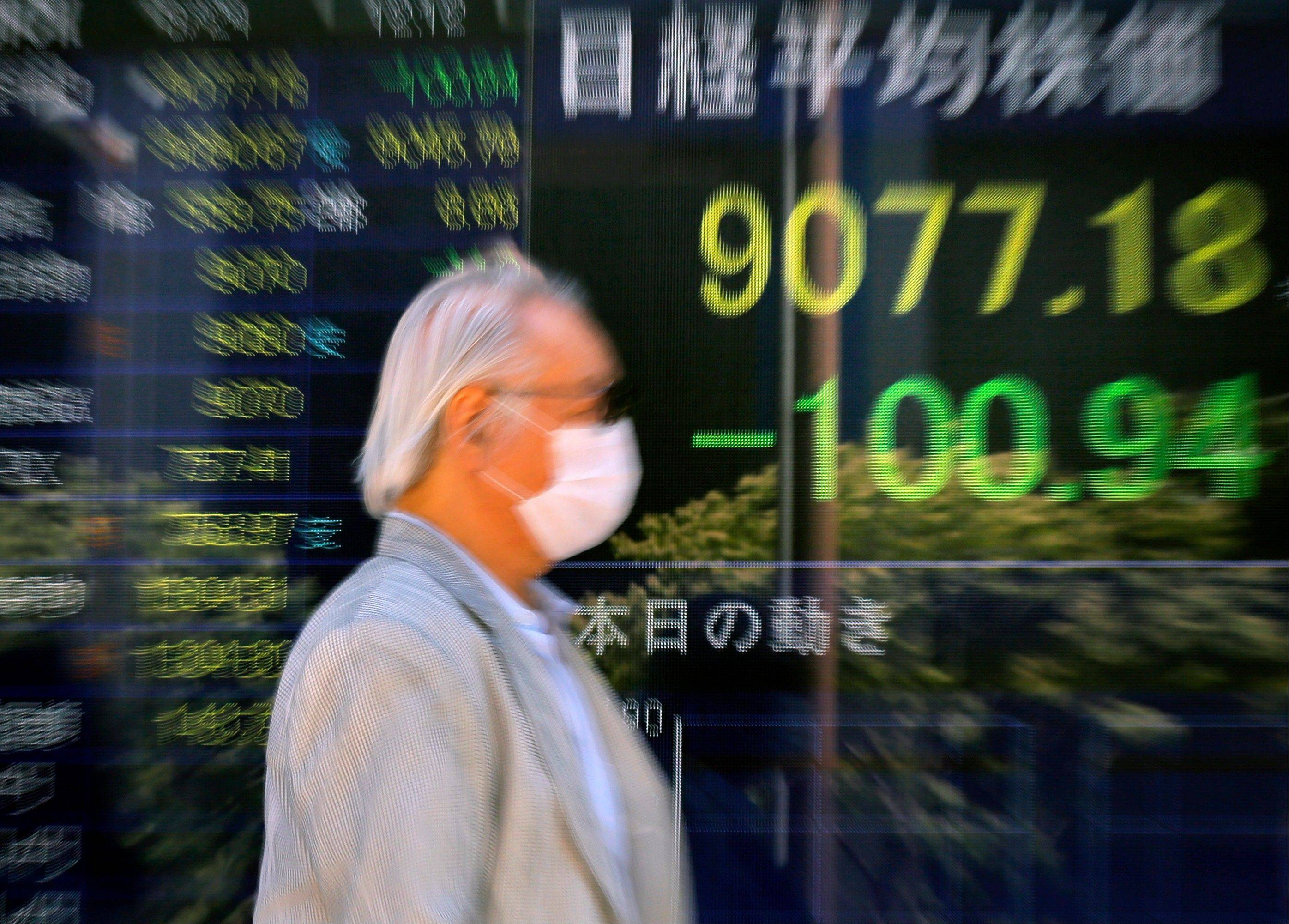 A man walks in front of the electronic stock board of a securities firm in Tokyo.