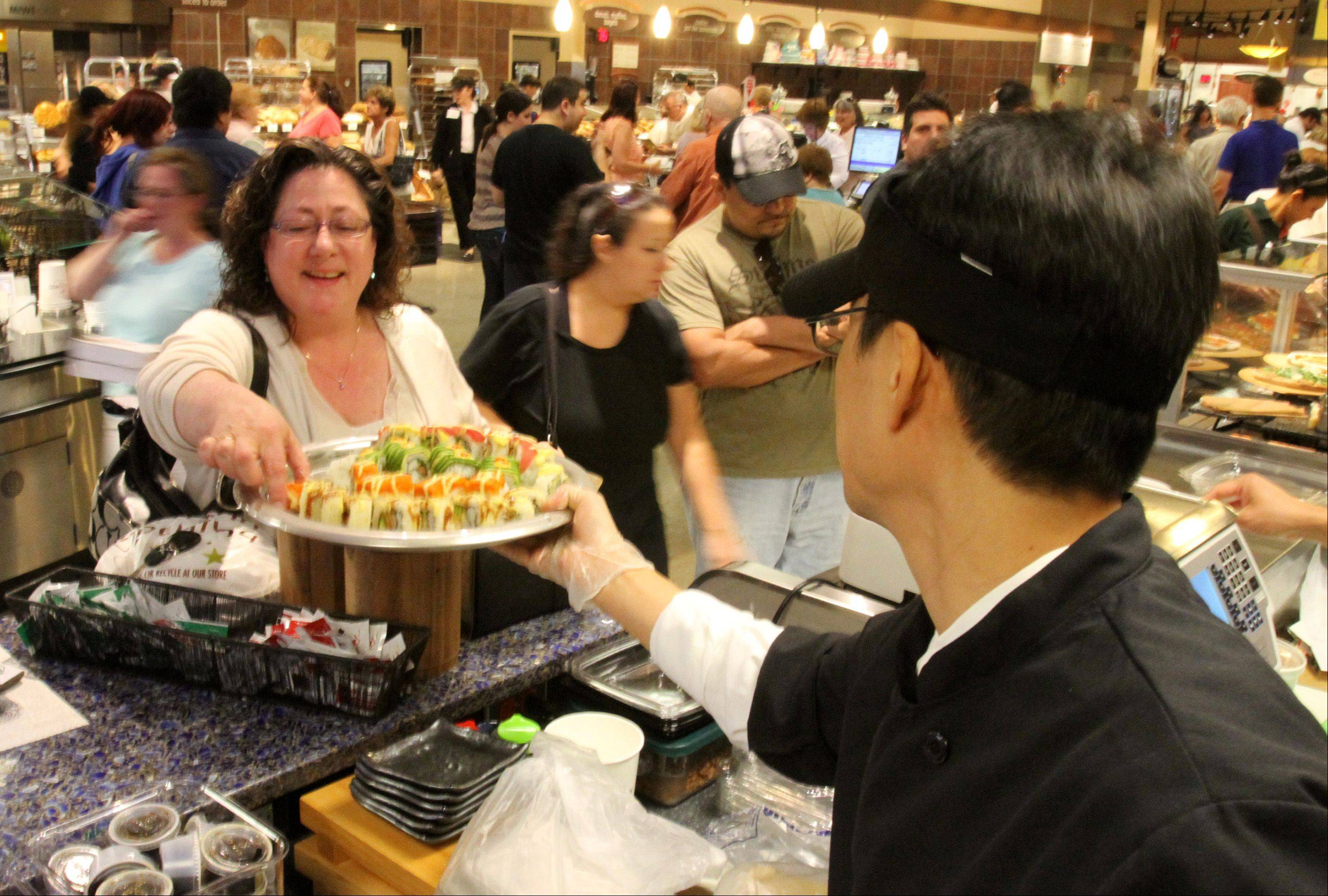 Laura Johnson of Elgin samples sushi from Brandon Lee at Mariano's Fresh Market in Hoffman Estates on Tuesday.