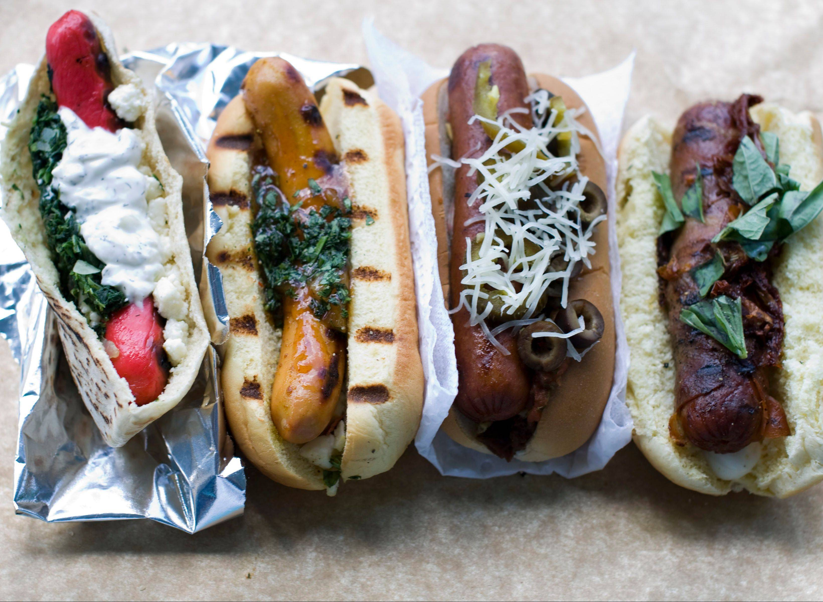 Dress up your dogs for Labor Day. Try toppings inspired by, from left, Greek spanakopita, Indian curry, taco and pizza.