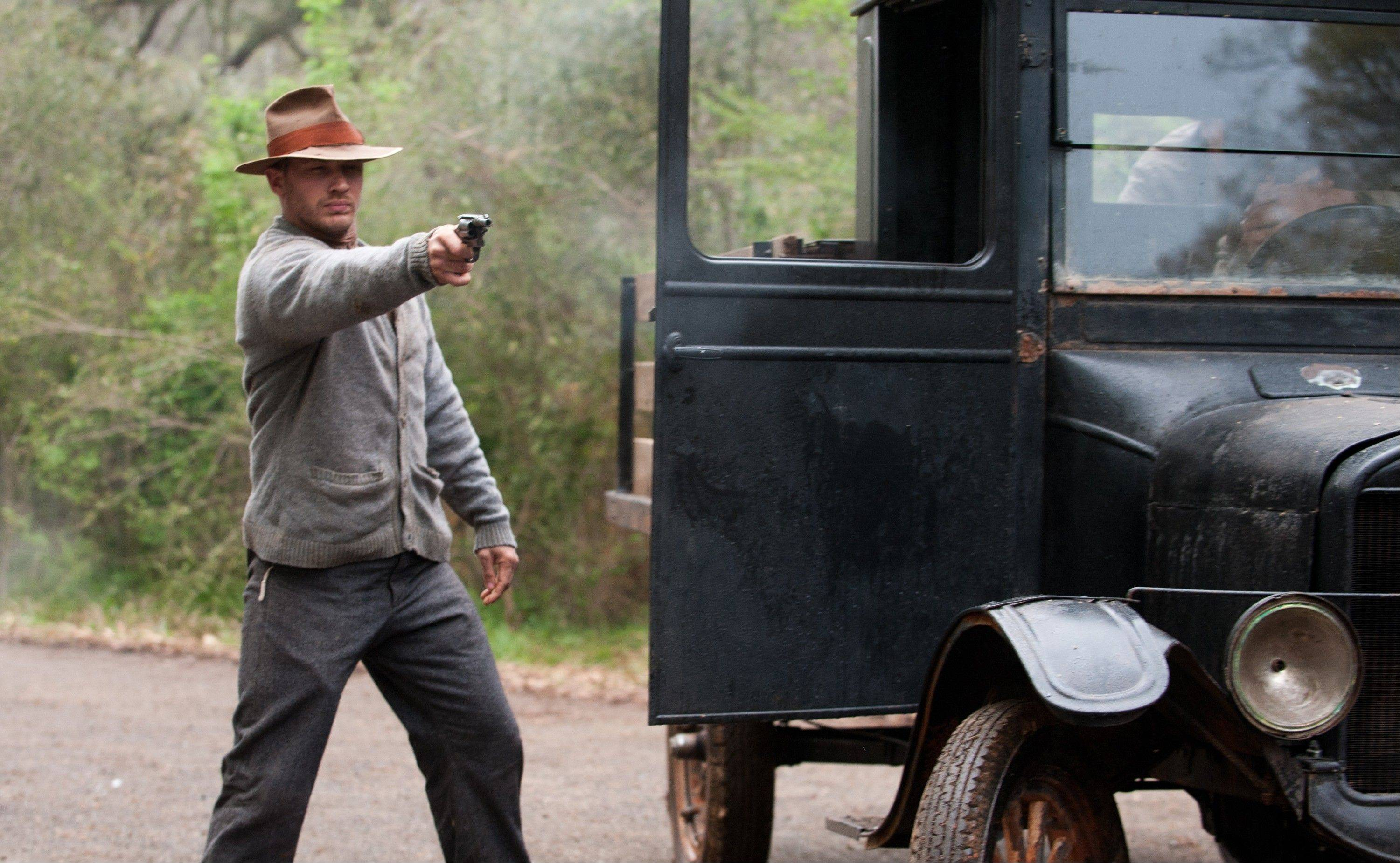 "Forrest (Tom Hardy) takes aim at law officers during a highway skirmish in the Prohibition-era crime drama ""Lawless,"" based on a family history."