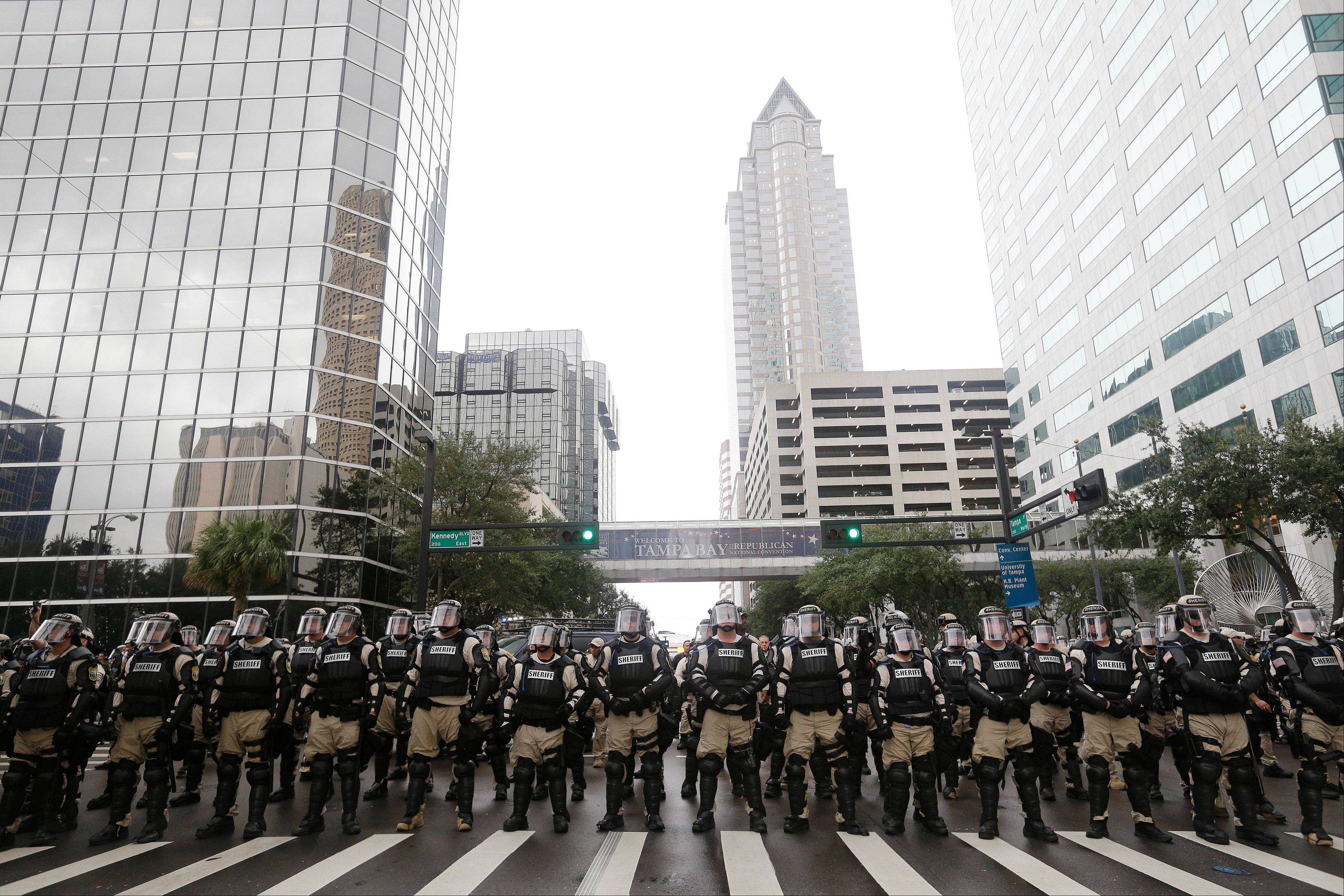 Police officers watch demonstrators marching through the streets of Tampa, Fla., to protest the Republican National Convention on Monday. Here's what tens of thousands of visitors in Tampa during the Republican National Convention will see this week: police. Lots of them.