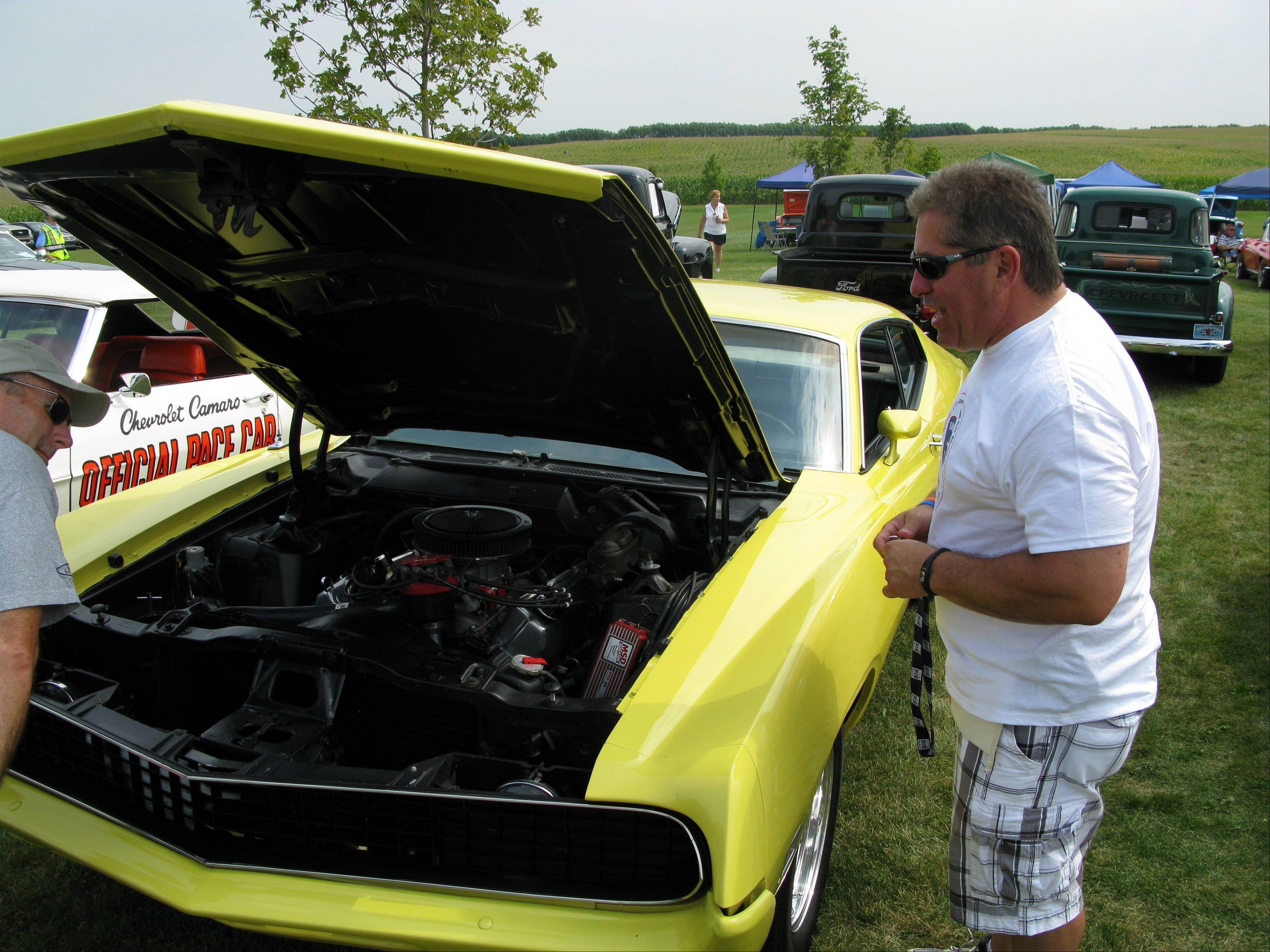 Kane County Sheriff Pat Perez traded stories with fellow classic car buffs last September at his annual car and motorcycle show for charity. Perez, right, is the proud owner of a yellow Ford Torino.