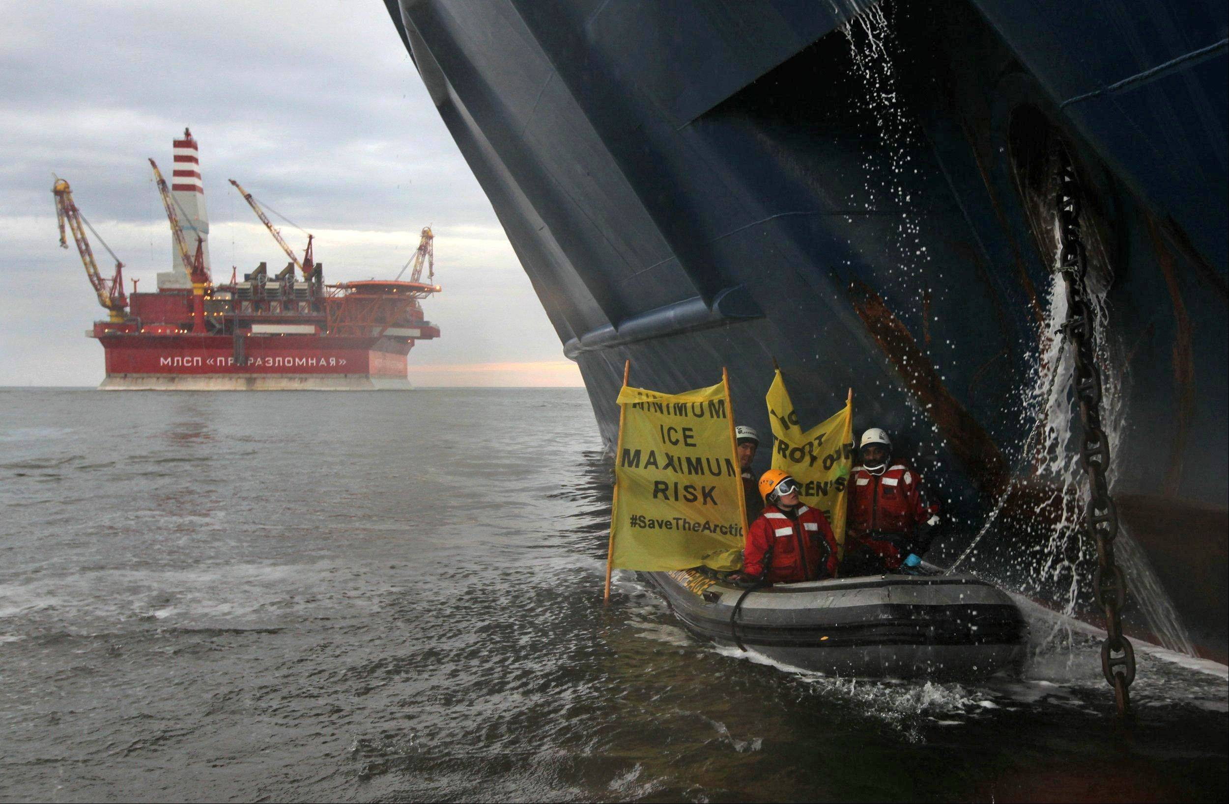 This image made available by environmental organization Greenpeace shows Greenpeace activists chained to the anchor chain of the Anna Akhmatova, the vessel which was carrying Gazprom's workers to the Prirazlomnaya platform, in the Pechora Sea about 620 miles from the nearest port. Gazprom is pioneering Russia's oil drilling in the Arctic.