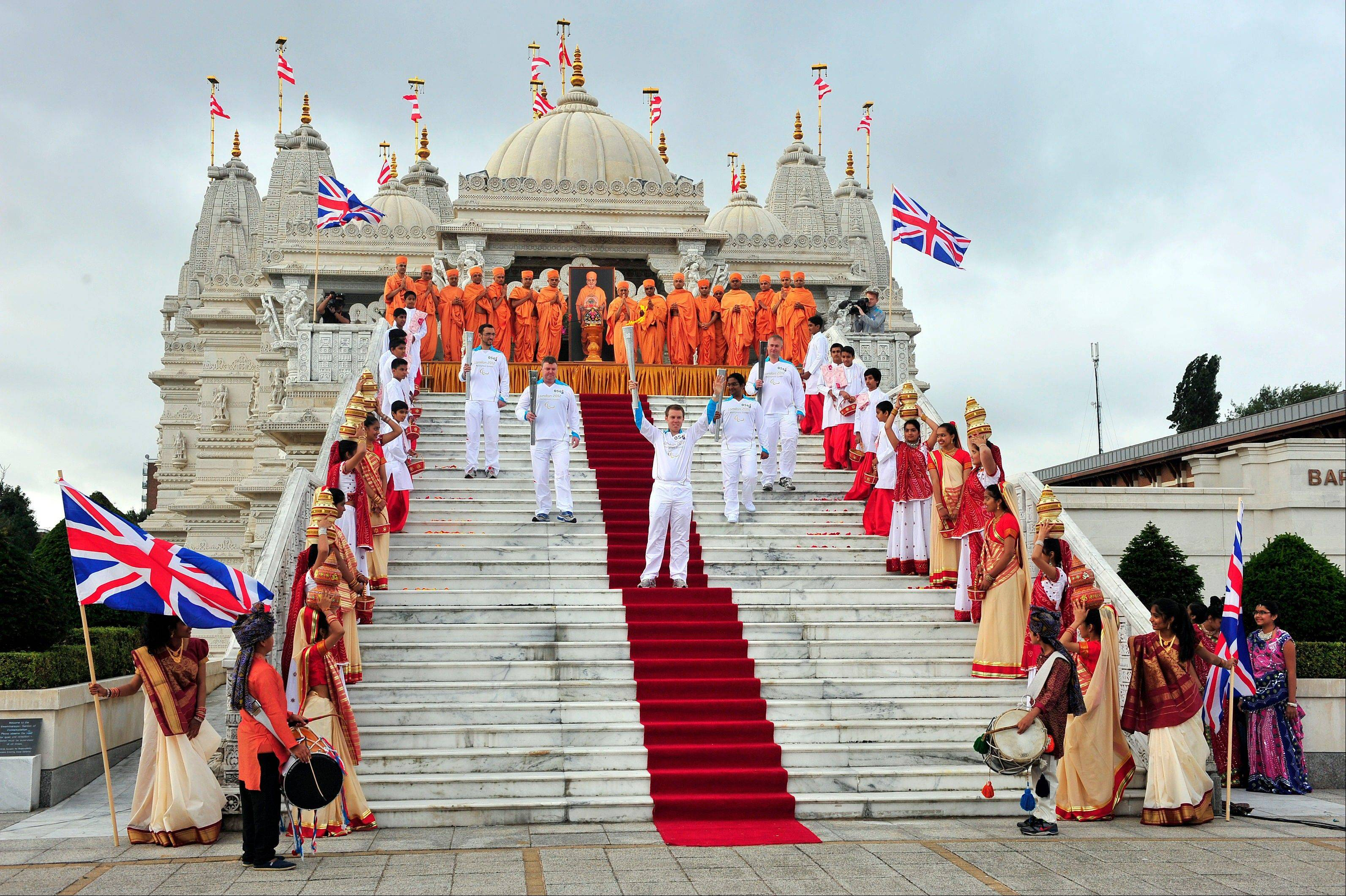 This photo made available by LOCOG shows Torchbearing team 056, (NOT left to right) including, Barrie Guy, Antony Eames, and others, no names available, outside the Shri Swaminarayan Mandir temple, in Brent, north London, as they carry the Paralympic Flame on the Torch Relay, Wednesday Aug. 29, 2012.