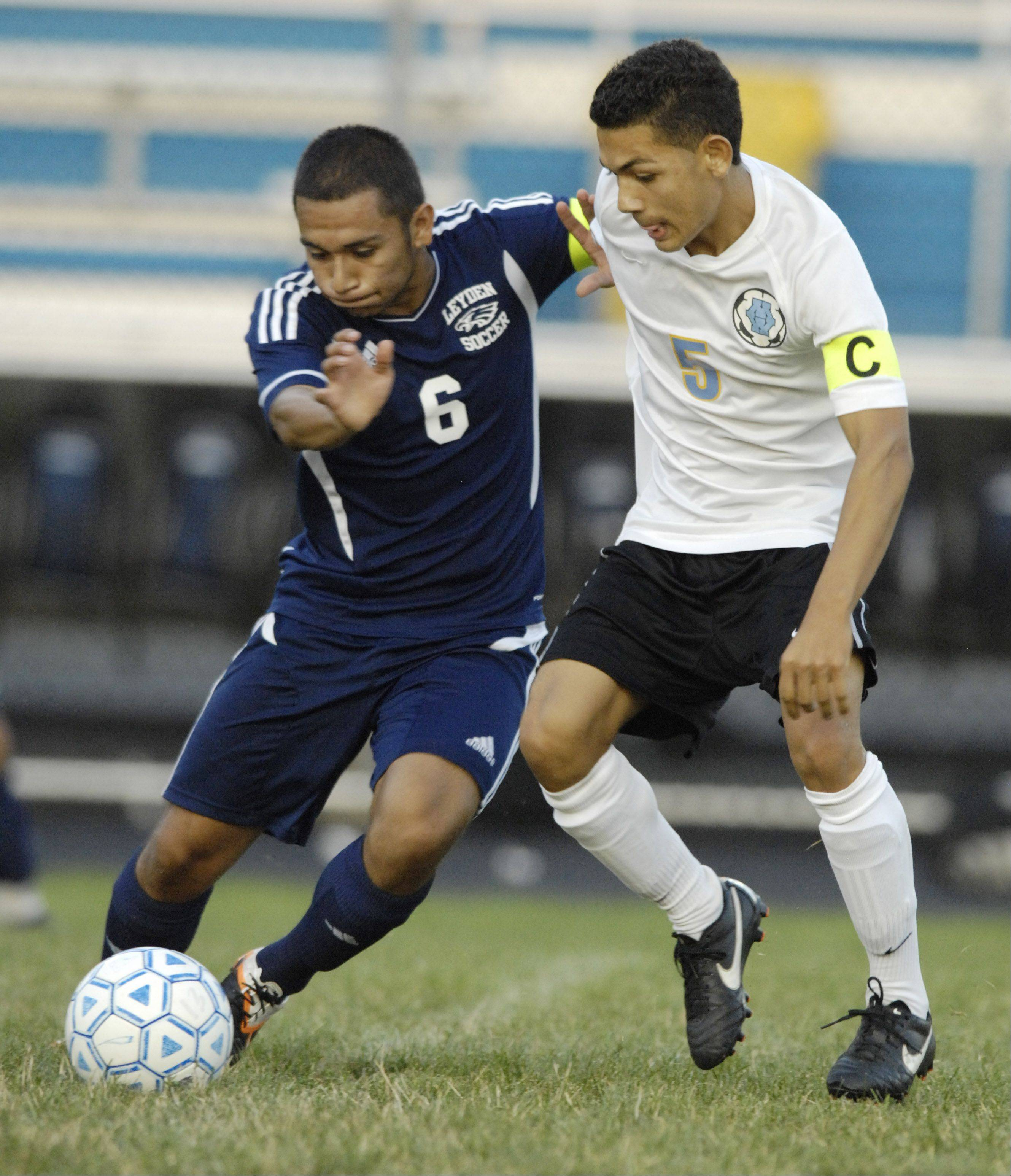 Leyden's Juan Recendez, left, and Maine West's Jerry Espinoza battle for position during Wednesday's game.