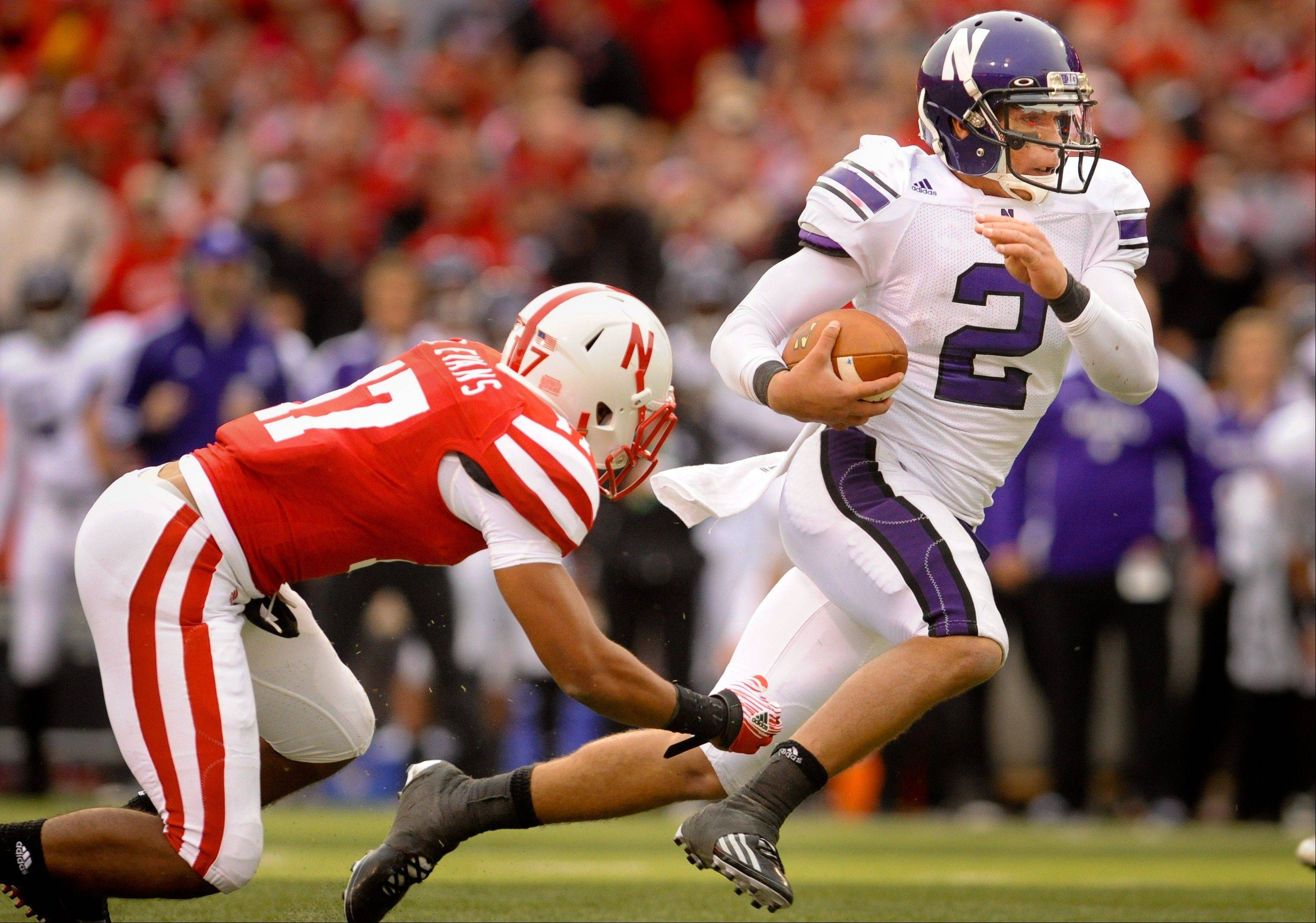 Northwestern's Kain Colter (2) slips by Nebraska's Ciante Evans (17) during an NCAA football game, Saturday Nov. 5, 2011, in Lincoln, Neb.