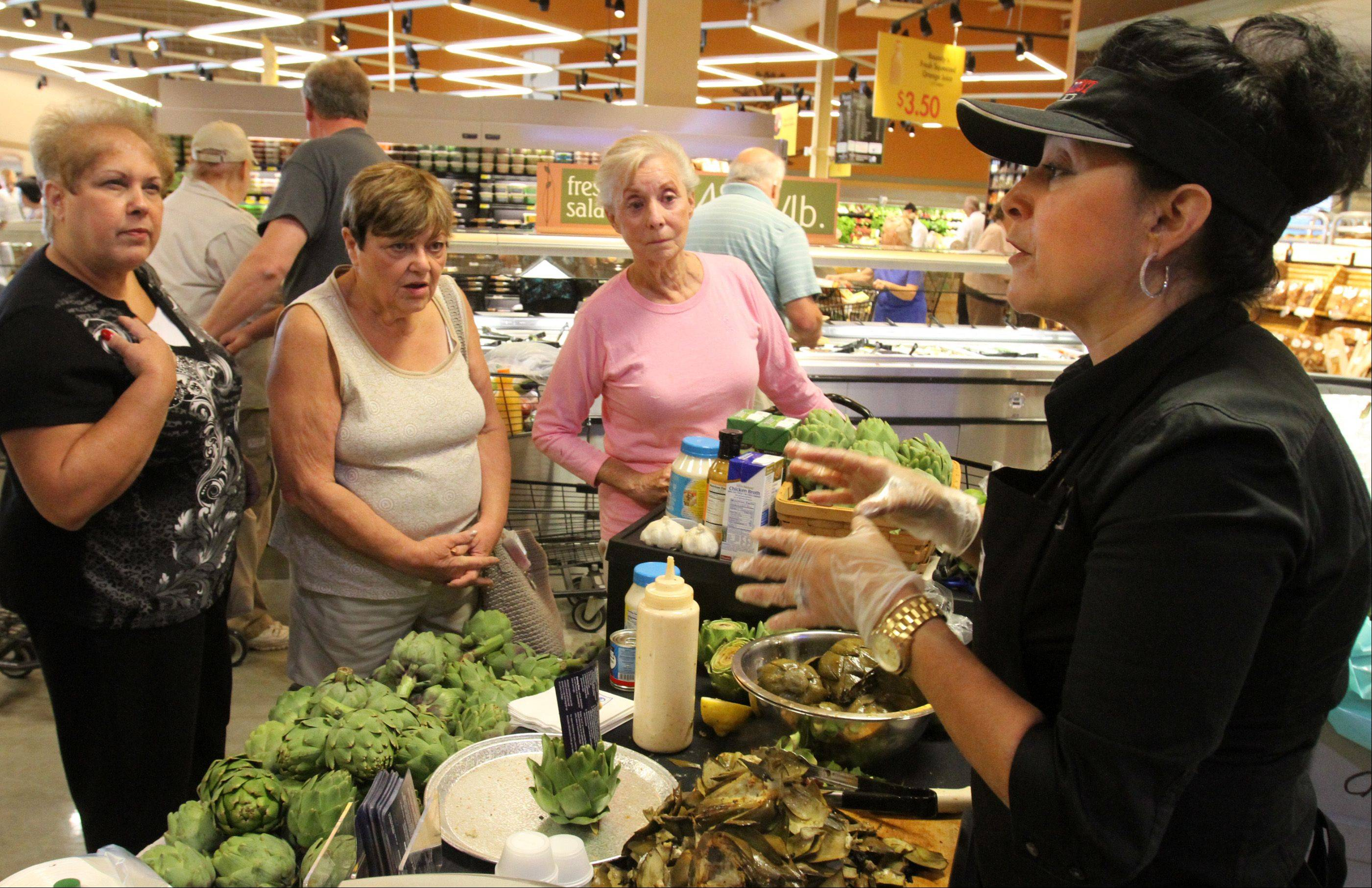 Adrienne Meier, a recipe designer with Ocean Mist, right, explains cooking tips for artichoke to customers including Jenny Hulseberg of Bartlett, center-right, at Mariano's Fresh Market in Hoffman Estates on Tuesday.