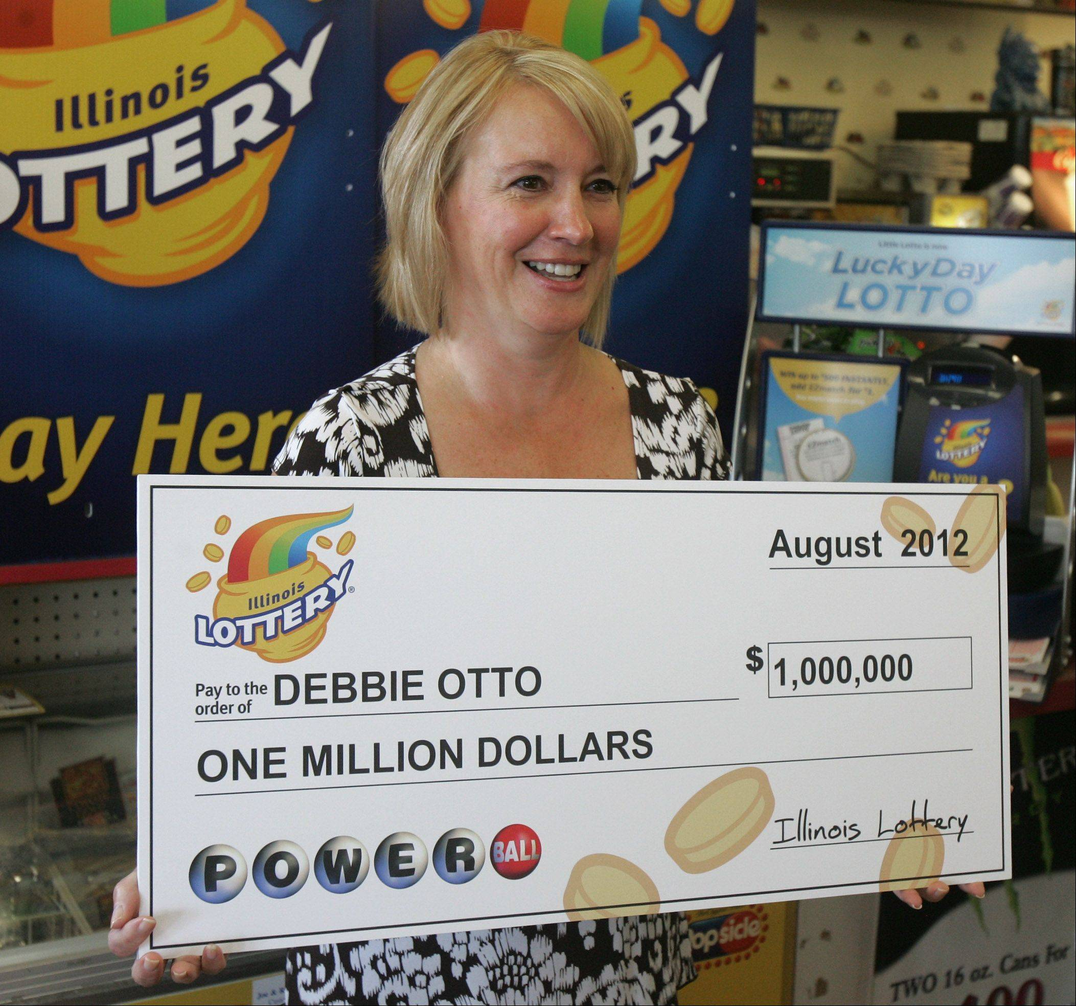 Debbie Otto, of Antioch Township, receives her $1 million Powerball prize Wednesday at Antioch Kwik Pantry.
