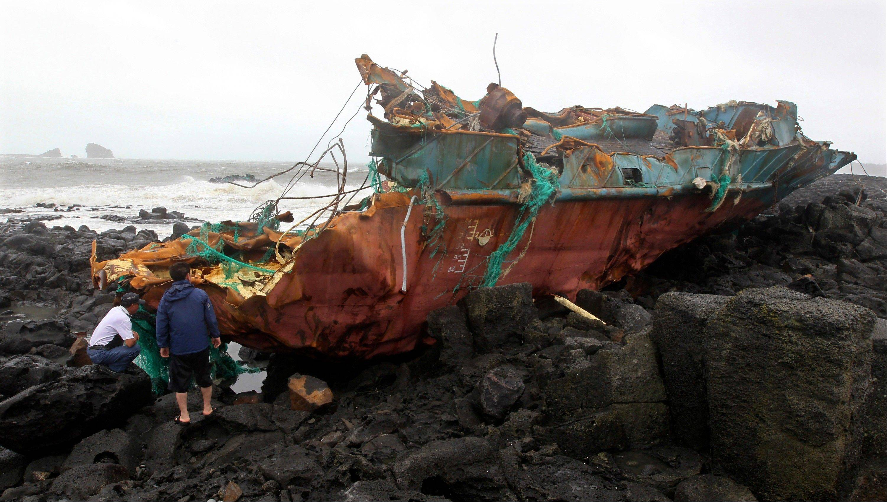 Wreckage of a Chinese ship sits on the shore after it slammed into rocks off the southern coast in Jeju, South Korea, Tuesday, Aug. 28, 2012. A powerful typhoon pounded South Korea with strong winds and heavy rain Tuesday, while the nation's coast guard battled rough seas in a race to rescue fishermen on two Chinese ships that slammed into rocks off the southern coast.