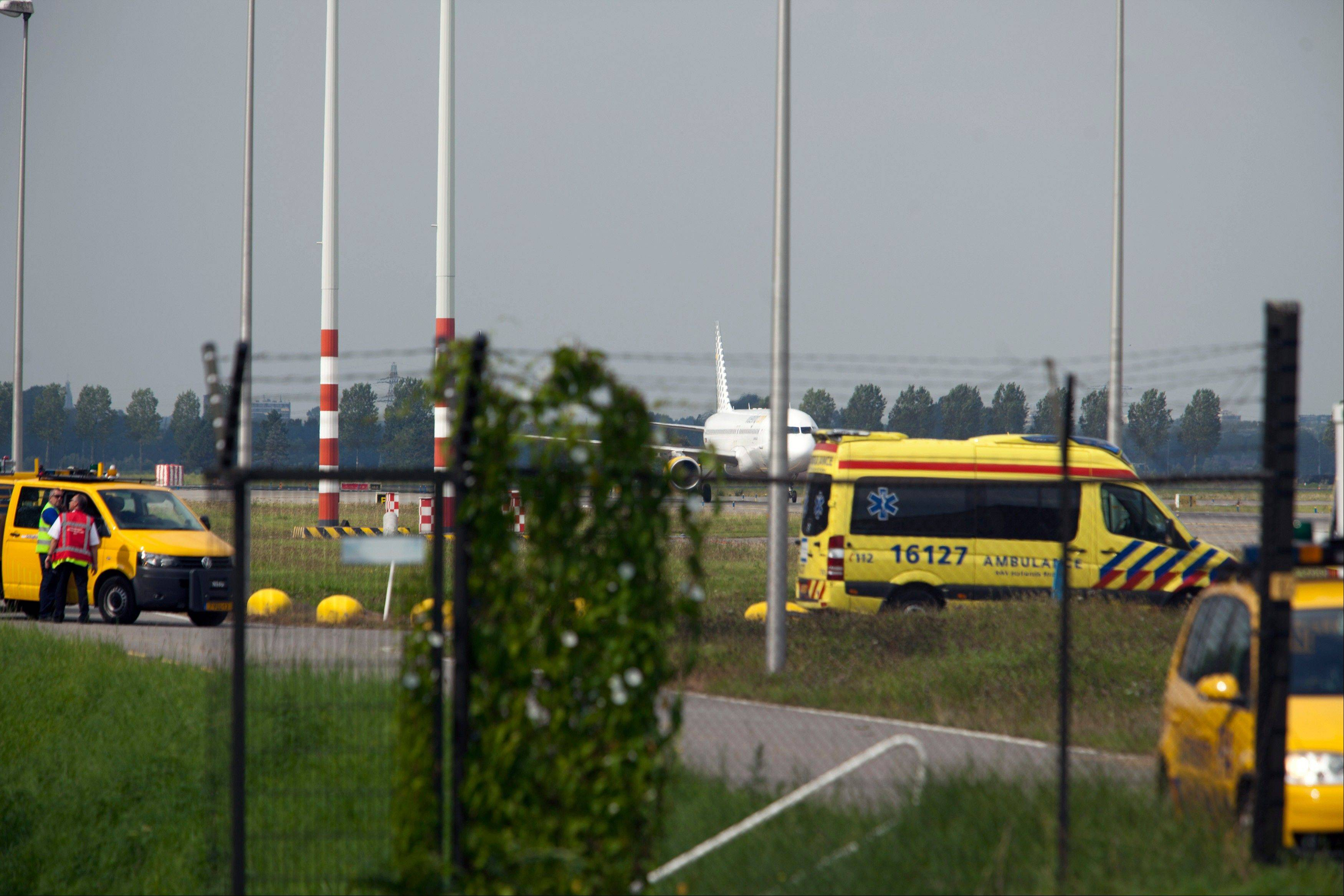 An ambulance is seen in front of a passenger plane from Malaga in Spain at Amsterdam's Schiphol Airport, Netherlands, Wednesday, Aug. 29, 2012. A news website reported that the plane was escorted to Schiphol on Wednesday by two F16 fighter jets and that the plane is from carrier Vueling. Dutch media now say the passenger plane from Spain to Amsterdam was not hijacked.