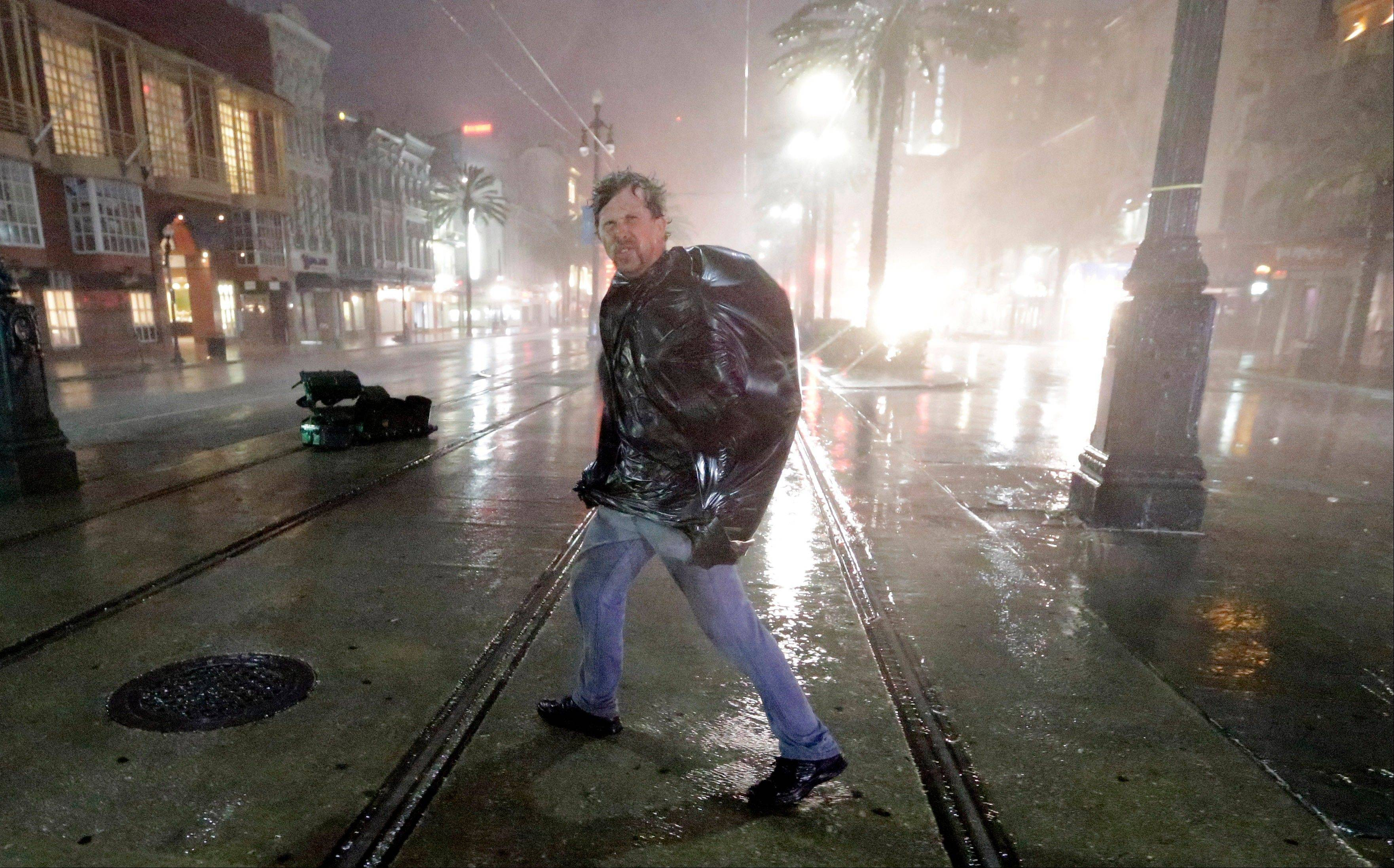 A man crosses Canal Street in the wind and rain from Hurricane Isaac Wednesday, Aug. 29, 2012, in New Orleans.