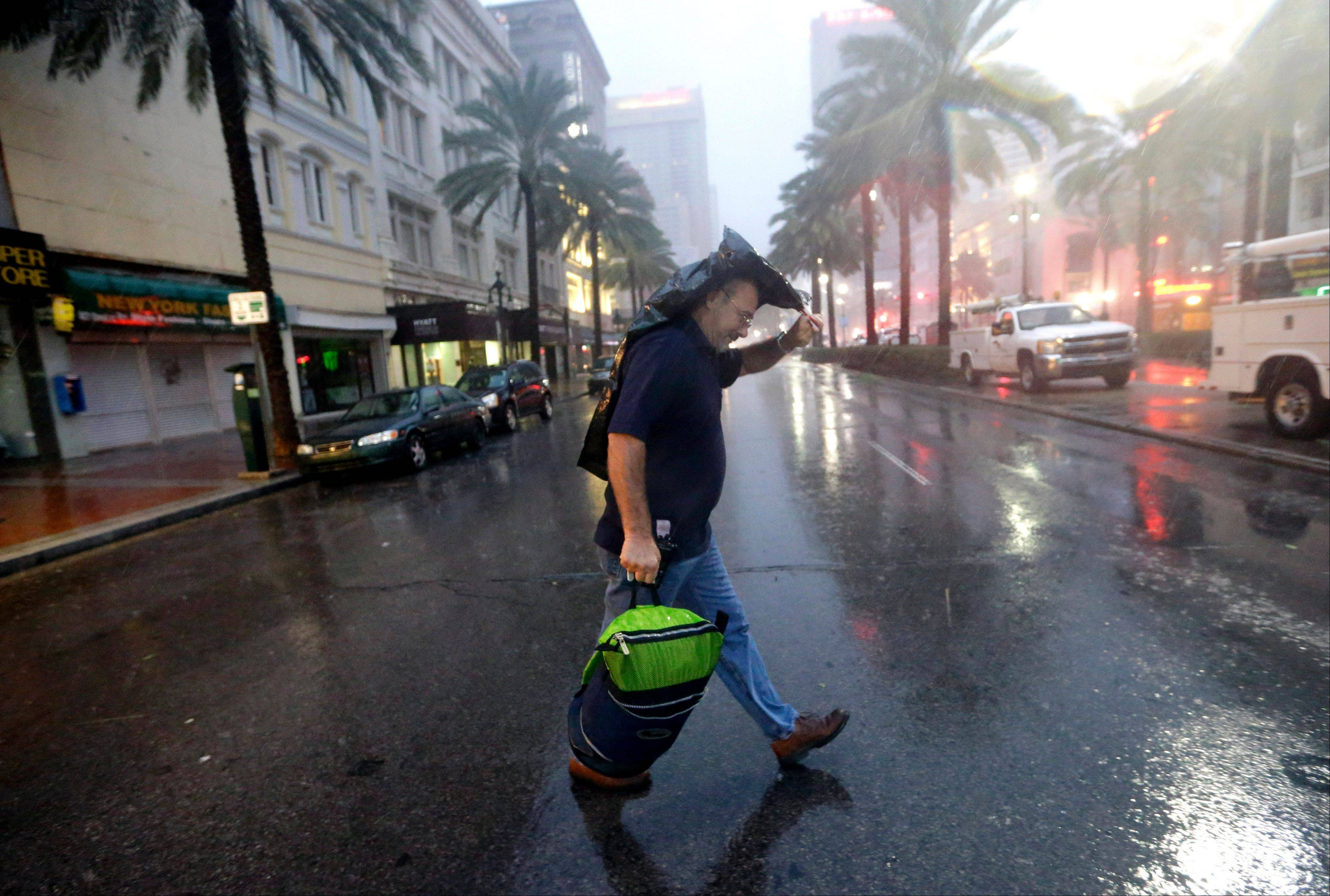 Ronnie Willis makes his way across Canal Street through the wind and rain from Hurricane Isaac Wednesday, Aug. 29, 2012, in New Orleans.