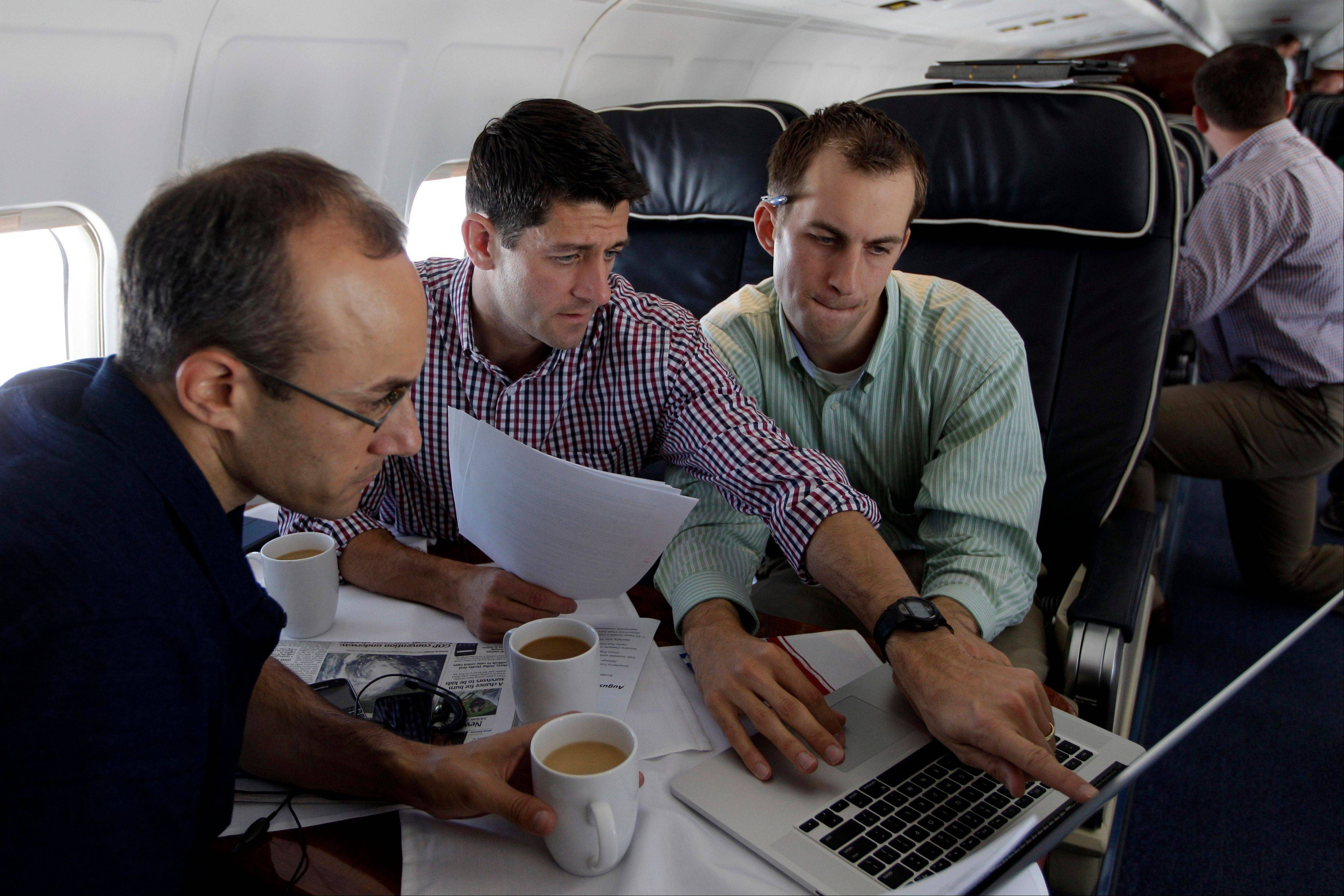 Republican vice presidential candidate Paul Ryan, center, of Wisconsin, works on the speech he will deliver at the Republican National Convention with senior adviser Dan Senor, left, and senior aide Conor Sweeney. during the campaign charter flight from Wisconsin to Tampa on Tuesday.