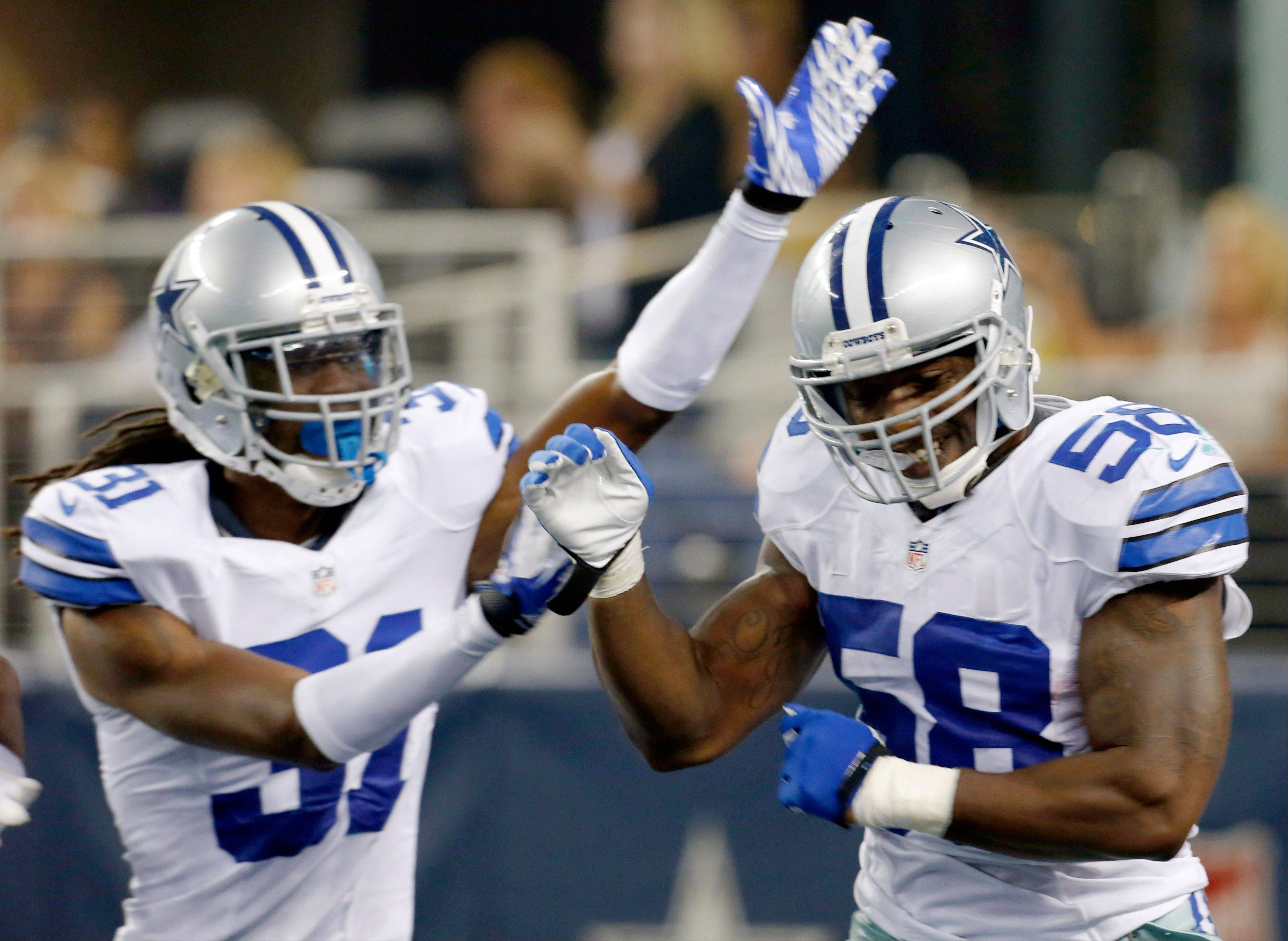Dallas Cowboys linebacker Orie Lemon (58) celebrates after scoring a touchdown from an interception thrown by Miami Dolphins quarterback Matt Moore with Cowboys defensive back Mario Butler, left, during the first half of a preseason NFL football game Wednesday in Arlington, Texas.