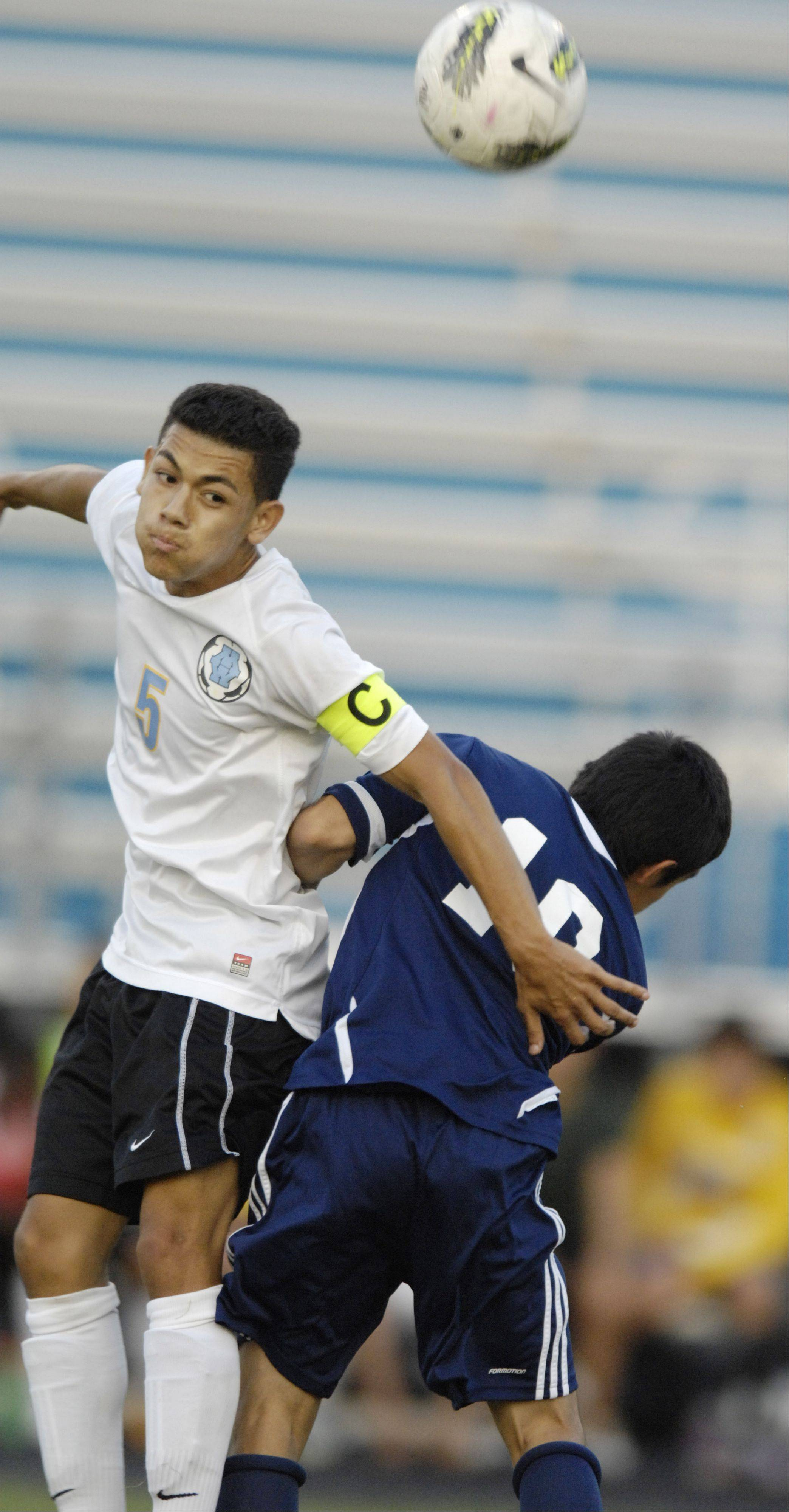 Maine West's Jerry Espinoza leaps for a header against Leyden.