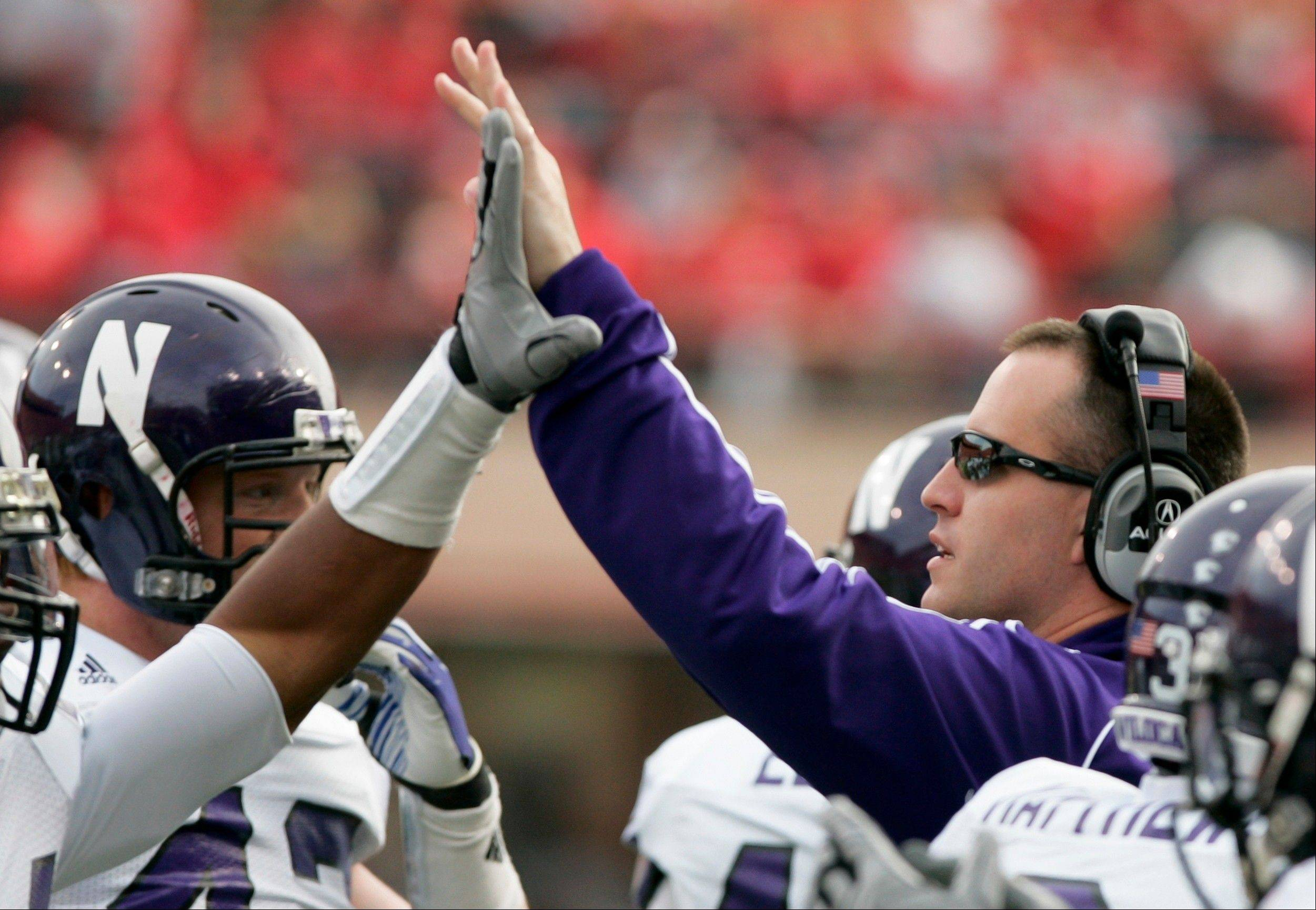 Northwestern head coach Pat Fitzgerald high-fives Ibraheim Campbell, who recovered a fumble against Nebraska last season. Campbell, a safety, was NU's leading tackler in 2011 and the Wildcats hope an improved linebacking core takes on that role this season.
