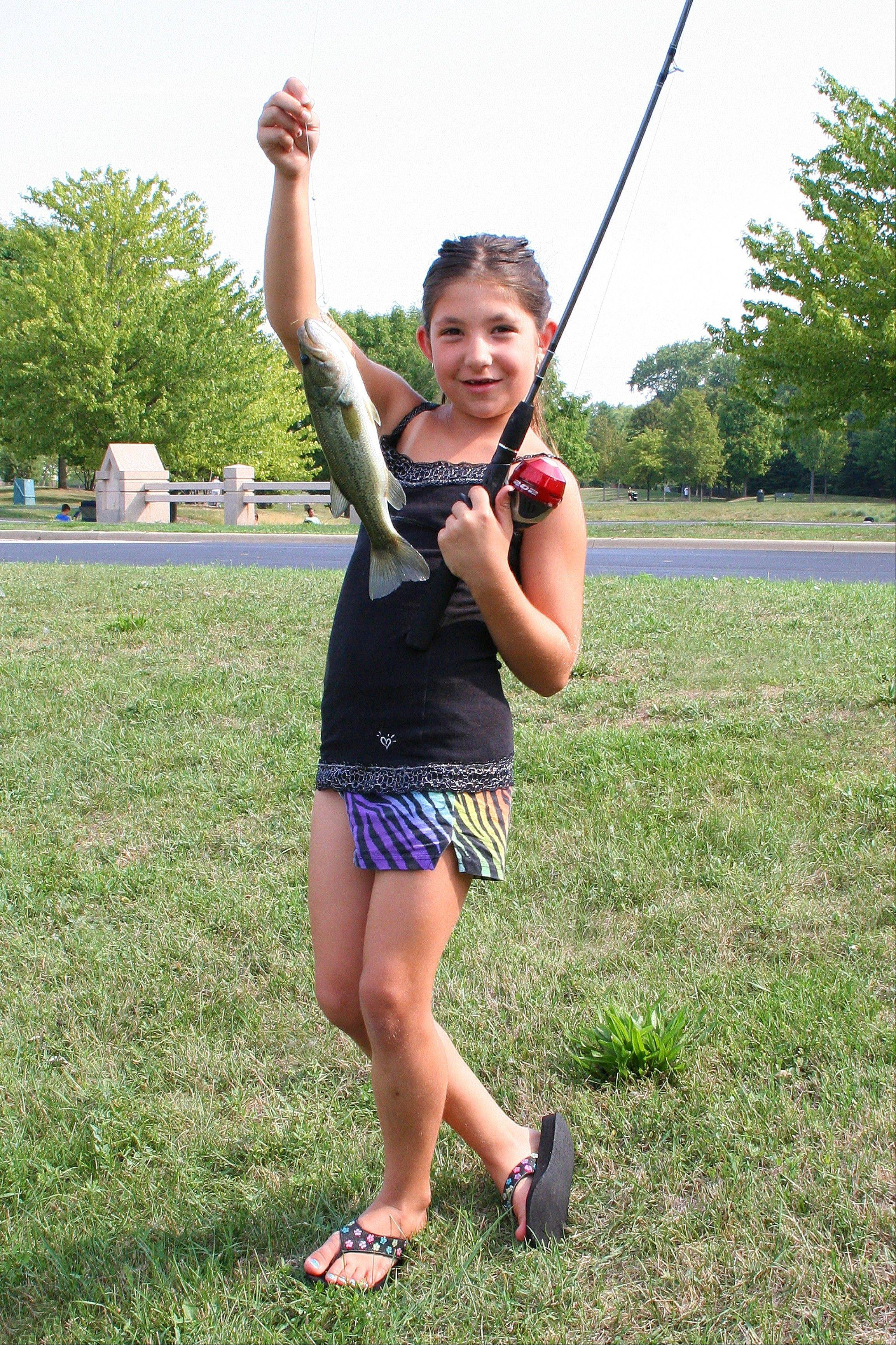 Cassidy Morisco holds up her 13-inch bass at the Family Fishing Derby at Mountain View Adventure Center on Aug. 4. It was not the biggest fish in her age group, but she also caught the smallest fish in the 6-8 age group, a 3.75-inch sunfish.