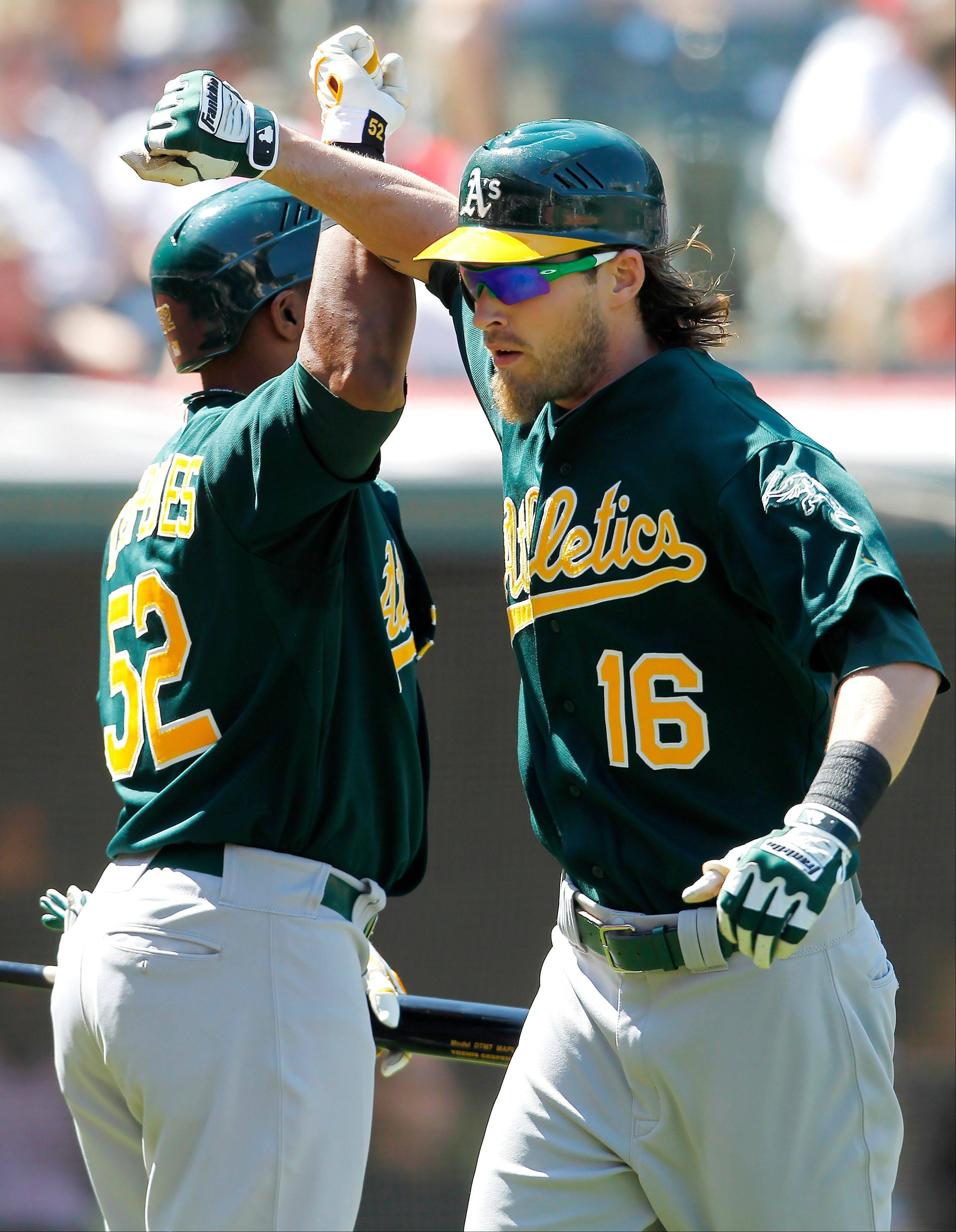 Oakland�s Josh Reddick, right, is greeted by Yoenis Cespedes after hitting a two-run home run off the Indians� Justin Masterson on Thursday in Cleveland.