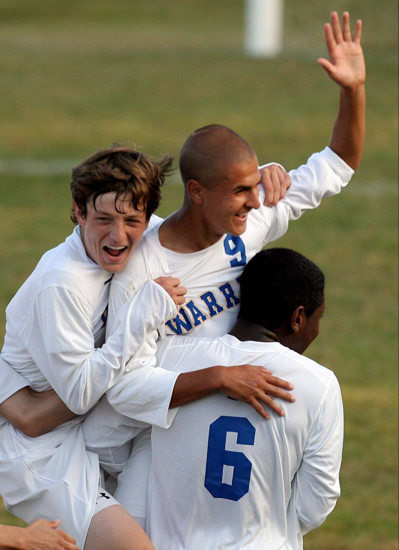 Warren�s Daniel Szczepanek, middle, is mobbed by teammates Alex Buvala, left and Leon Mardehow after Szczepanek�s second goal of last season�s North Suburban Conference title game against visiting Round Lake.