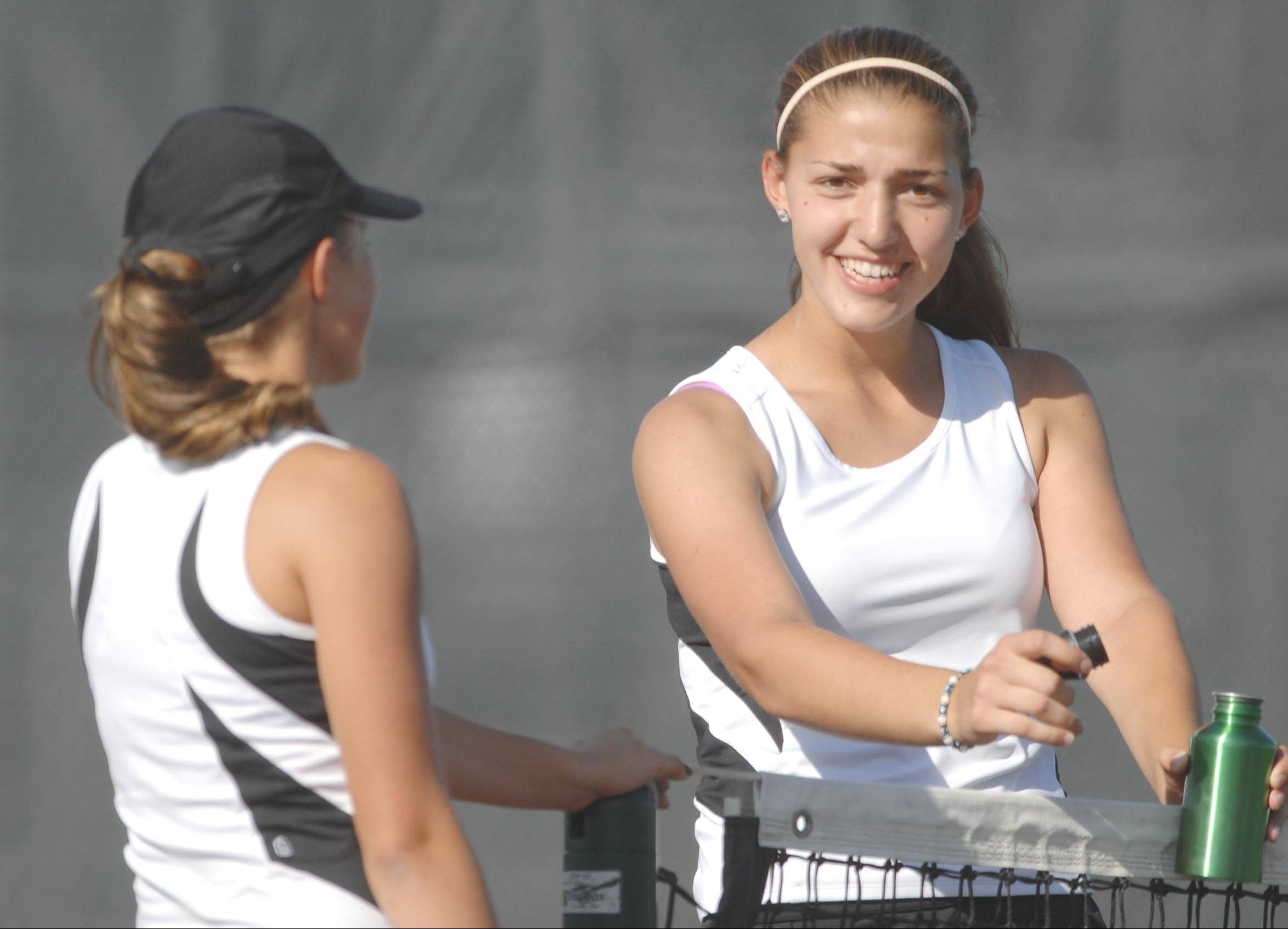 Kaneland�s Madison Jurcenko and Angelica Emmanouil, right, talk at the net late during a first doubles win over Mackenzie Schiff and Betsy Jones of Wheaton Academy earlier this month.