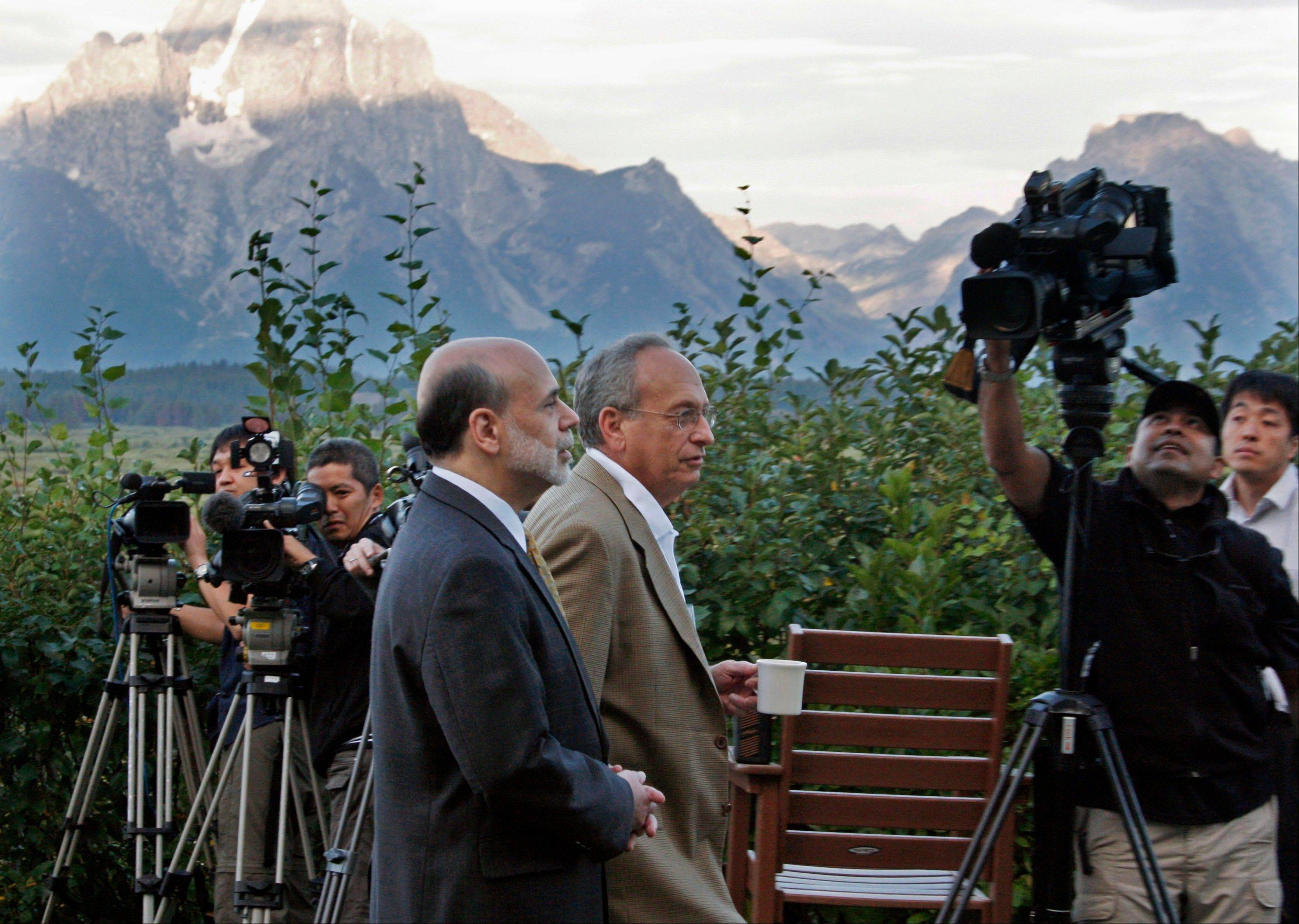 Federal Reserve chairman Ben Bernanke, left, and Donald L. Kohn, governor of the Federal Reserve Bank of Dallas, walk along the veranda of the Jackson Lake Lodge with the Grand Tetons in the distance, at the start of the annual Federal Reserve conference in Jackson, Wyo., on Aug. 27, 2010.