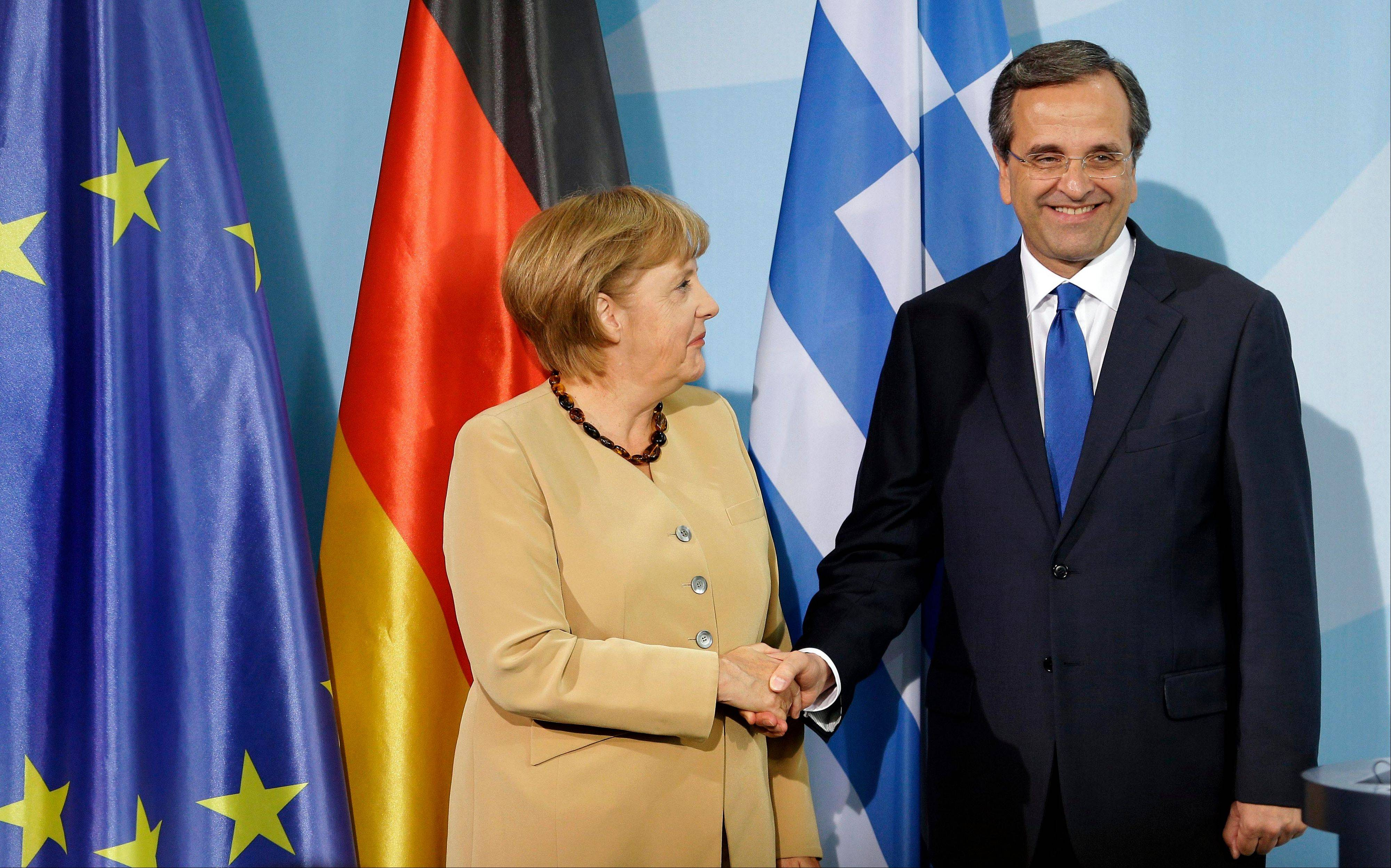 German Chancellor Angela Merkel and Prime Minister of Greece Antonis Samaras shake hands after a joint news conference as part of a meeting at the chancellery in Berlin, Germany.