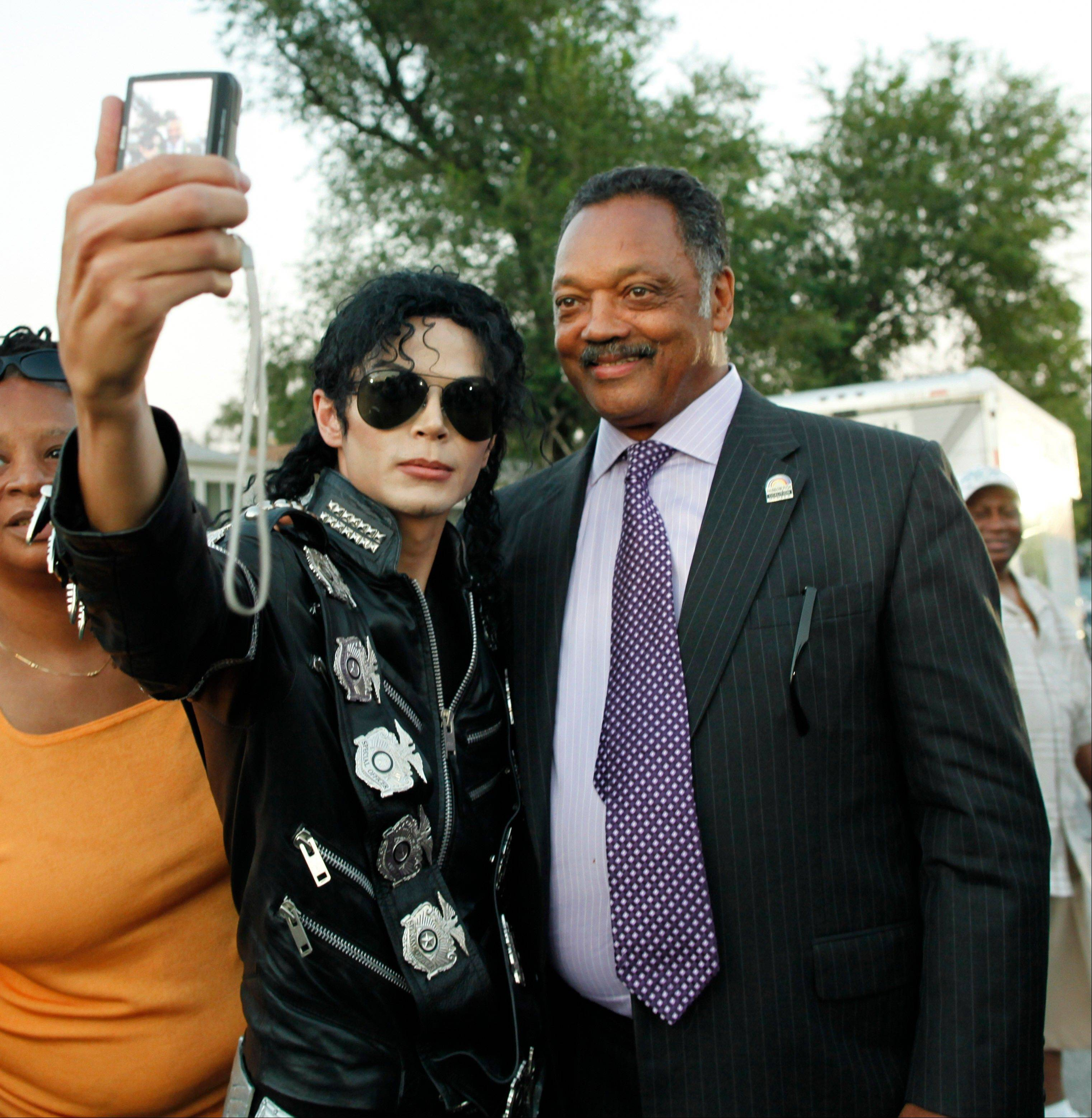 Michael Jackson impersonator Carlo Riley from Denver poses with Rev. Jesse Jackson near Michael Jackson's boyhood home in Gary, Ind., during a celebration marking what would have been Jackson's 54th birthday Wednesday.