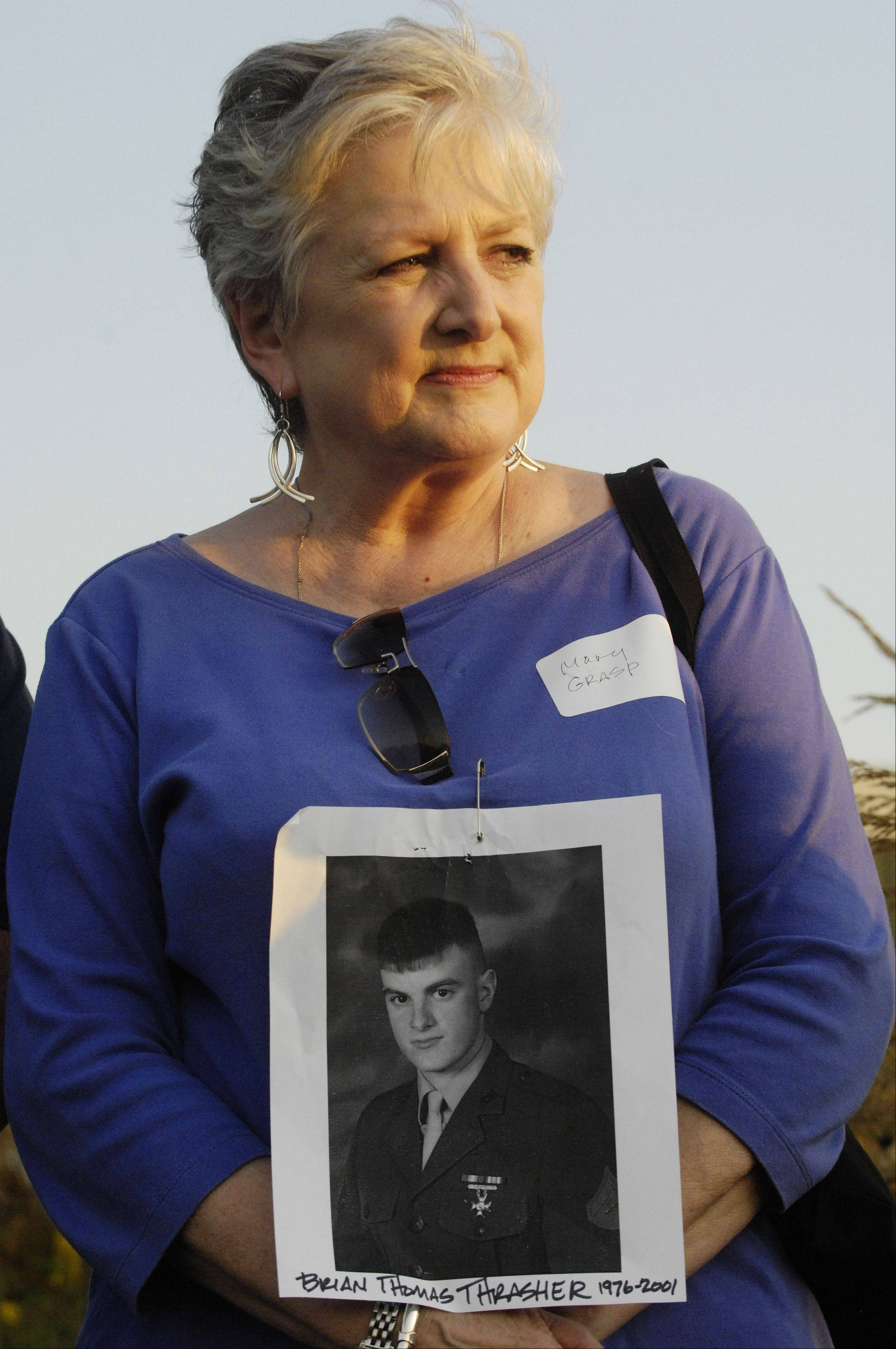 JOE LEWNARD/jlewnard@dailyherald.comMary Thrasher of Palatine holds a portrait of her son, Brian Thomas Thrasher, during a candlelight vigil and remembrance ceremony Thursday at Roosevelt University in Schaumburg. He died of a heroin overdose at age 25.