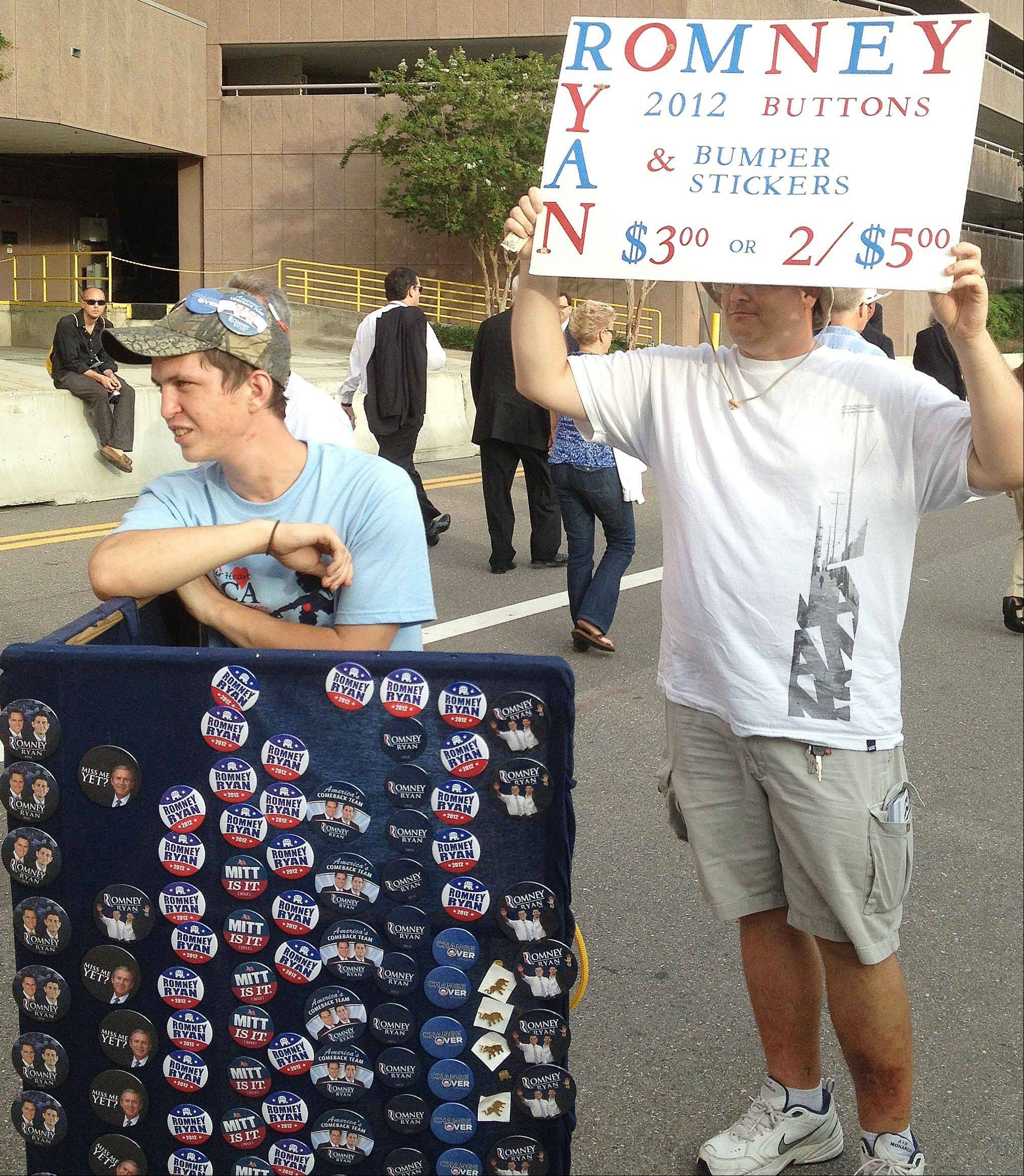 Michael Kirever, left, and Brian Judge, sell buttons of Republican presidential nominee Mitt Romney Wednesday outside the Republican National Convention in Tampa, Fla. While buttons are seen at the convention, they are far from ubiquitous, and the days when delegates were littered with partisan messages from seemingly head to toe appear to be long past.