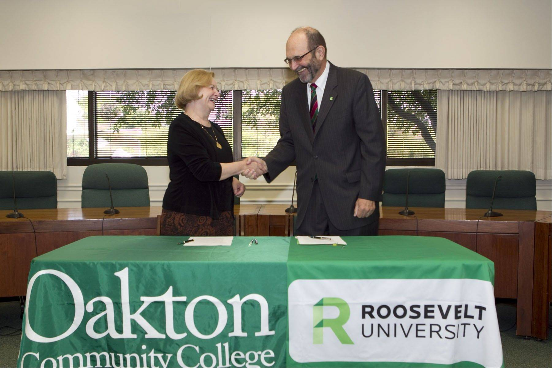 Oakton Community College President Margaret B. Lee and Roosevelt University President Chuck Middleton seal the deal with a handshake on Wednesday.