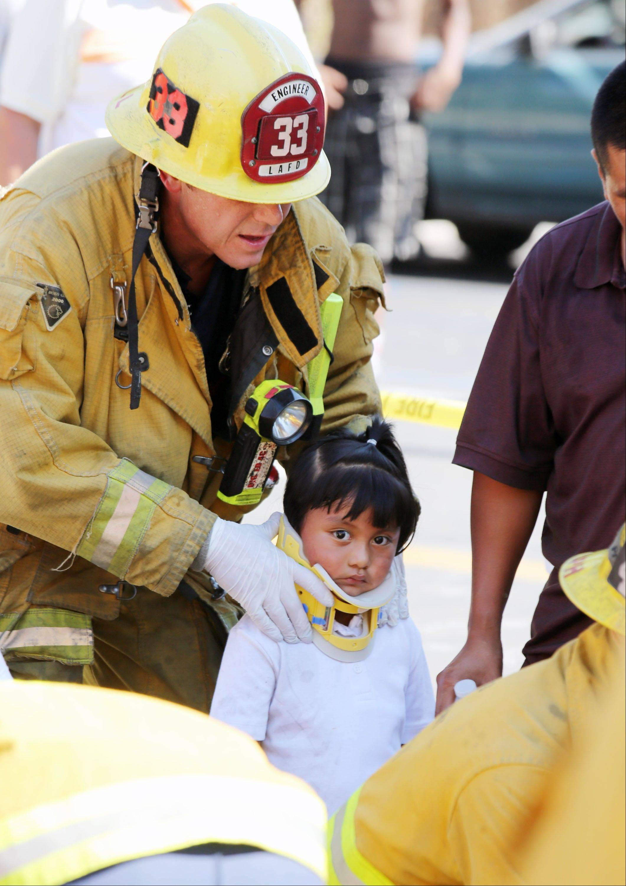 A Los Angeles City firefighter assists a child, one of eight people injured when a car sped onto a sidewalk and plowed into a group of parents and children outside Main Street Elementary school, Wednesday Aug. 29, 2012 in Los Angeles. The crash occurred at 2:50 p.m., shortly after school had let out for the day, according to a statement from the Los Angeles Unified School District.