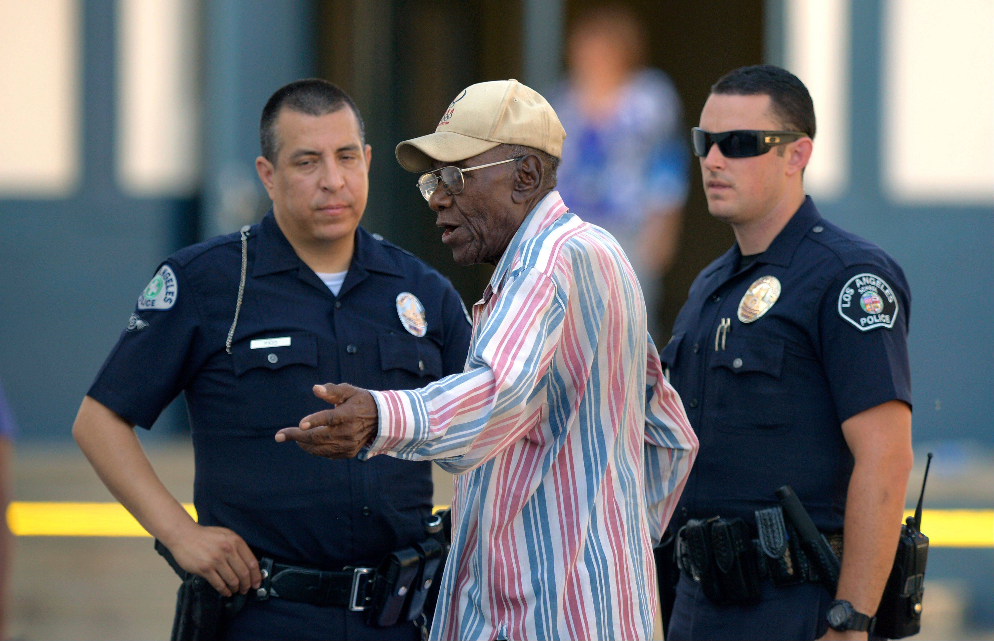 Preston Carter, 100, talks with police officers after police say his car went onto a sidewalk and plowed into a group of parents and children outside a South Los Angeles elementary school, Wednesday, Aug. 29, 2012, in Los Angeles. Nine children and two adults were injured in the wreck.