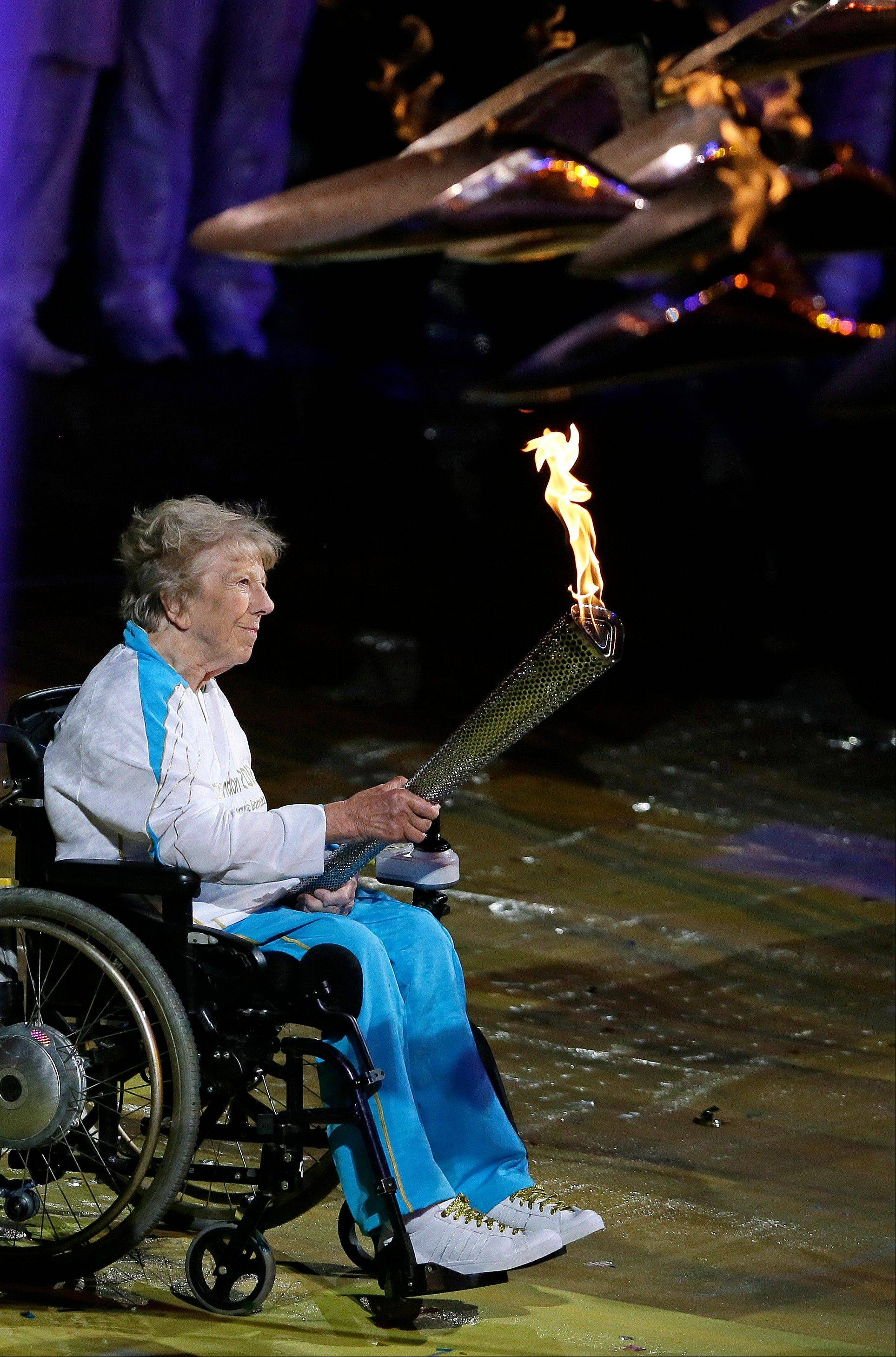 Margaret Maughan, Britain's first Paralympic gold medalist, lights the Paralympic flame during the Opening Ceremony for the 2012 Paralympics in London, Wednesday Aug. 29, 2012.