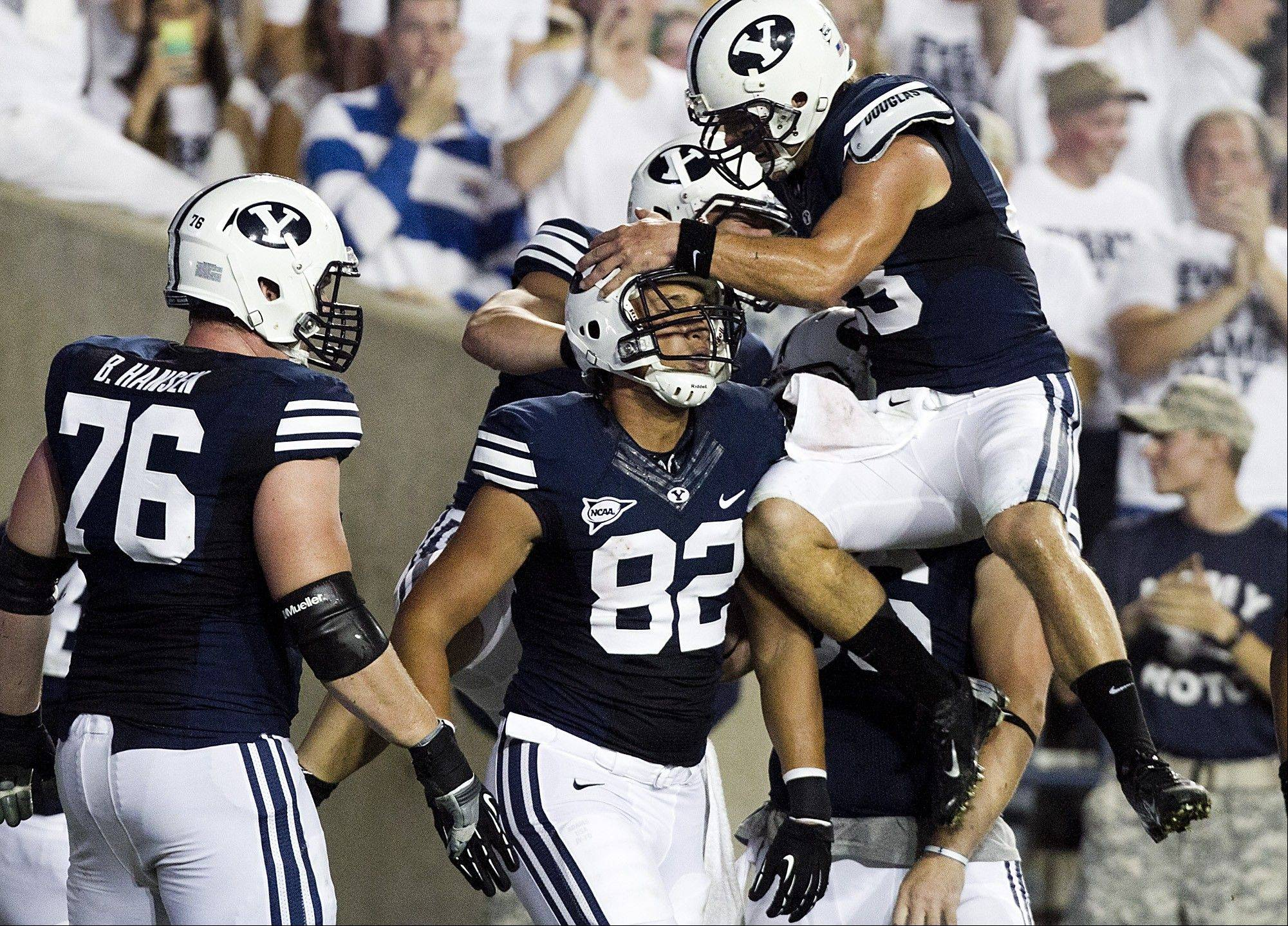 BYU's Kaneakua Friel, center, is congratulated by quarterback Riley Nelson after a touchdown against Washington State on Thursday in Provo, Utah.