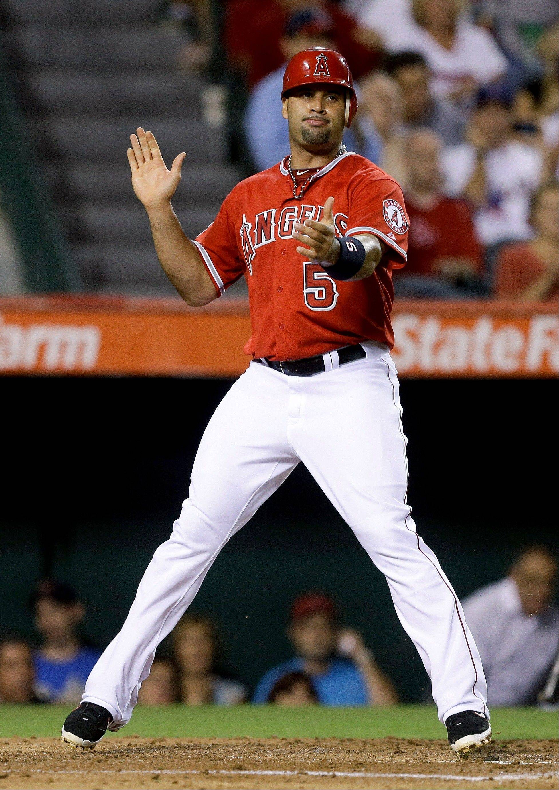 The Angels' Albert Pujols celebrates after scoring on a hit by Alberto Callaspo during the third inning against Boston on Thursday in Anaheim, Calif.