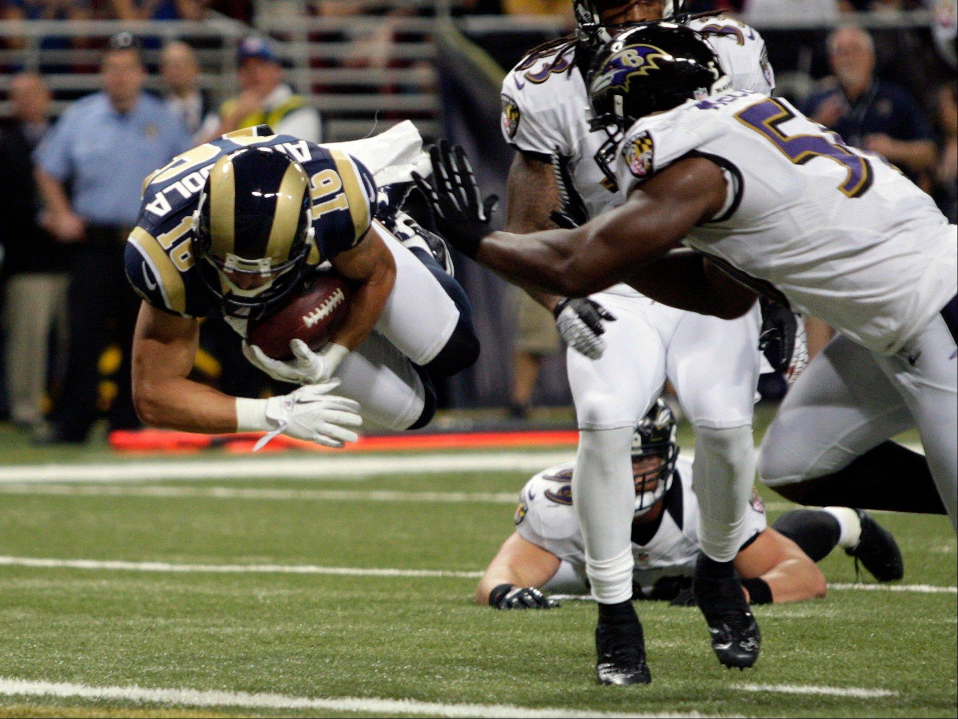 St. Louis Rams wide receiver Danny Amendola dives into the end zone past Baltimore Ravens linebacker Albert McClellan after catching a 7-yard pass for a touchdown during the first quarter of a preseason game Thursday in St. Louis.