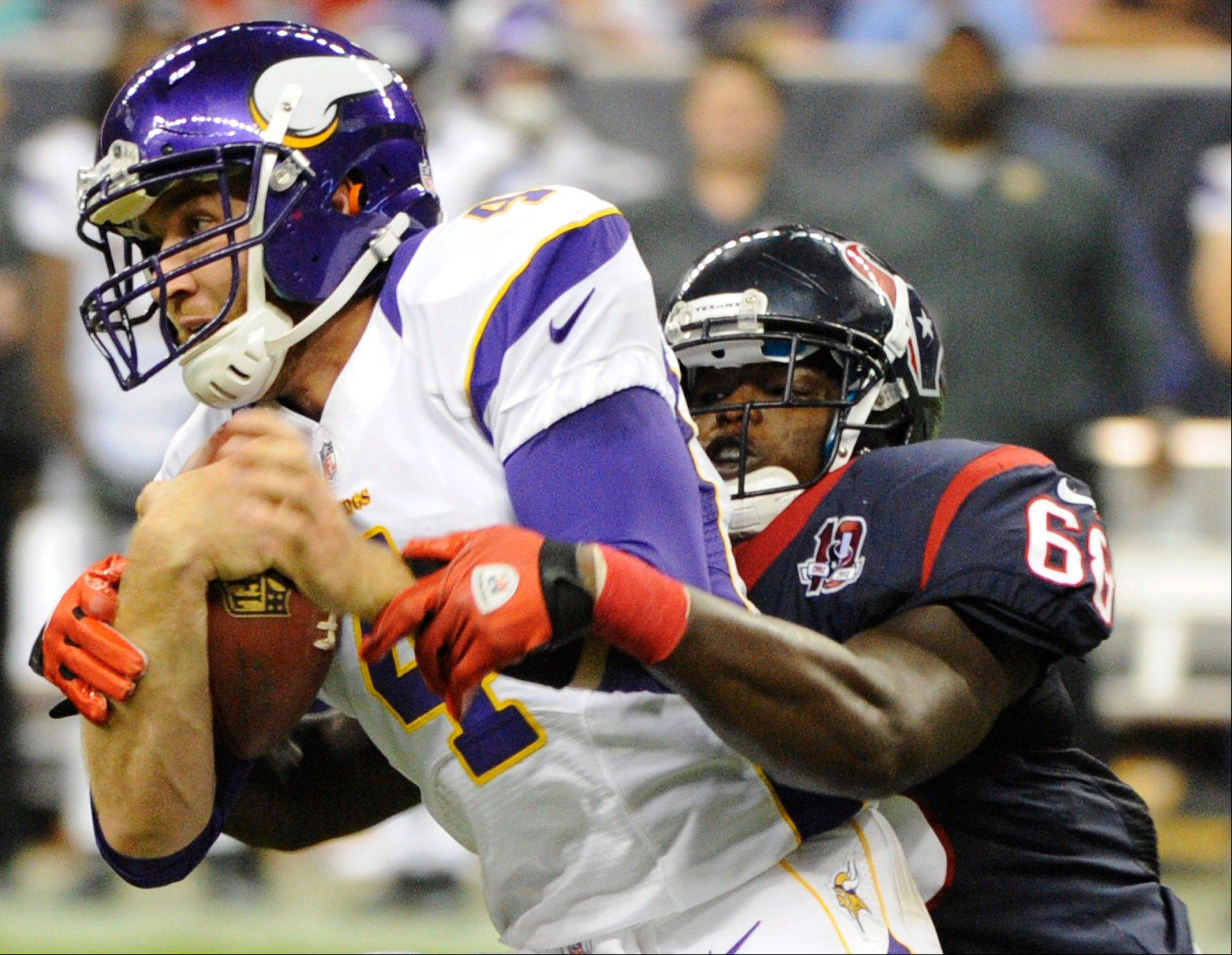 Houston Texans defensive tackle Rennie Moore wraps up Minnesota Vikings quarterback McLeod Bethel-Thompson during the second half of Thursday's preseason game in Houston.