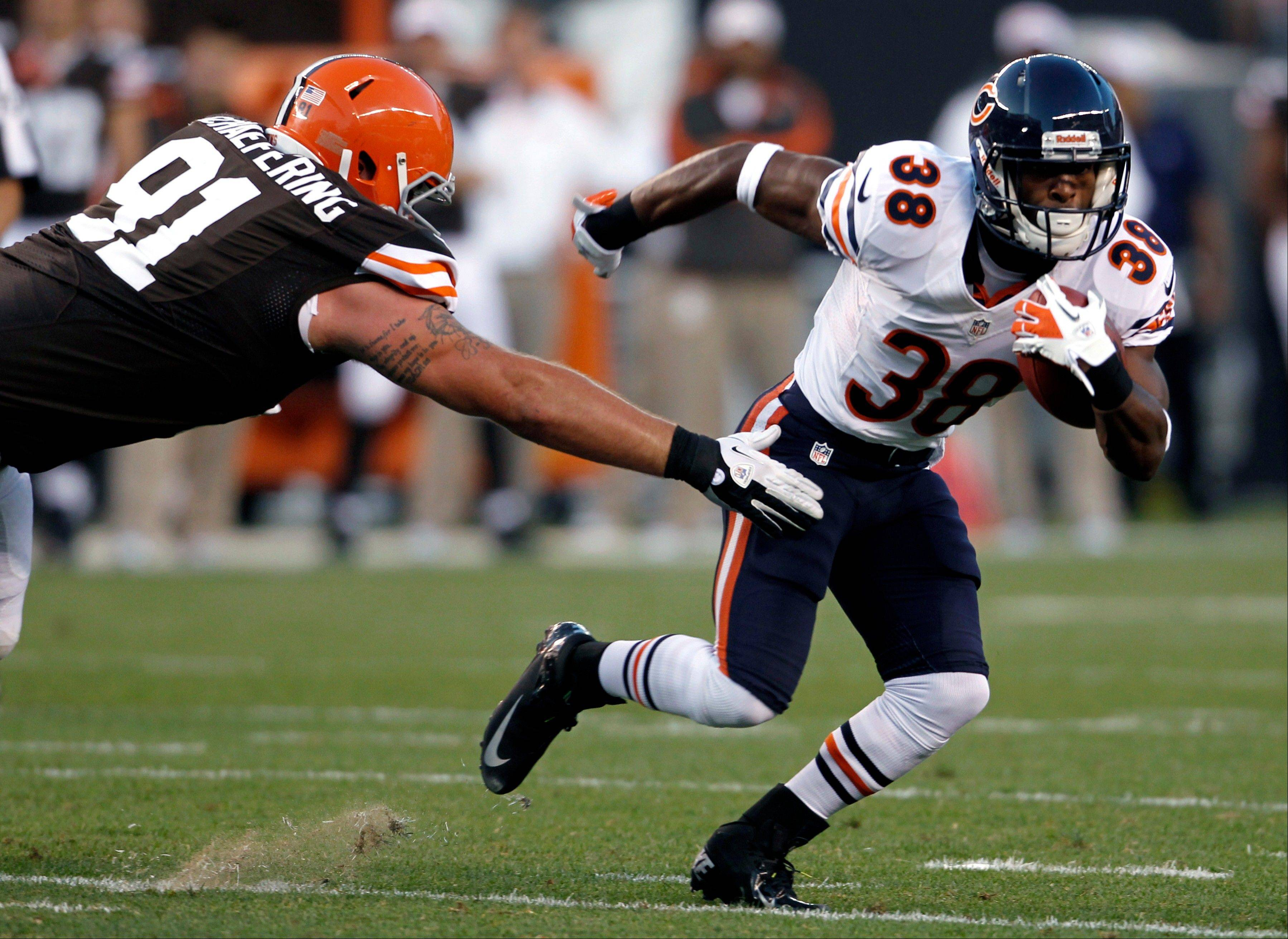 Chicago Bears running back Lorenzo Booker avoids the tackle by Cleveland Browns nose tackle Brian Schaefering in the first quarter of a preseason NFL football game Thursday, Aug. 30, 2012, in Cleveland.