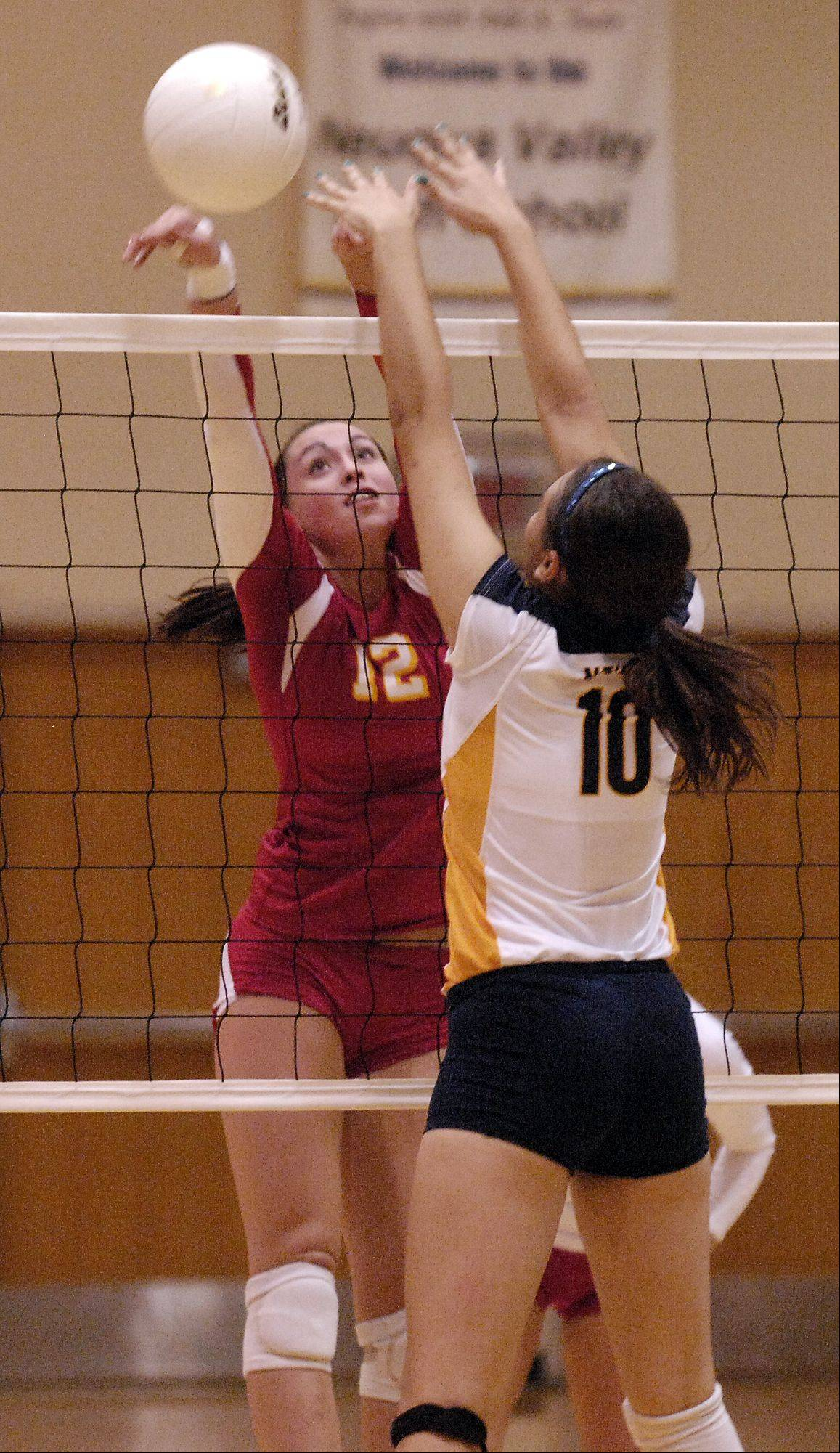 Shea Thayer of Batavia hits the ball past Stephanie Vas of Neuqua Valley during girls varsity volleyball in Naperville. Batavia won 2-0.