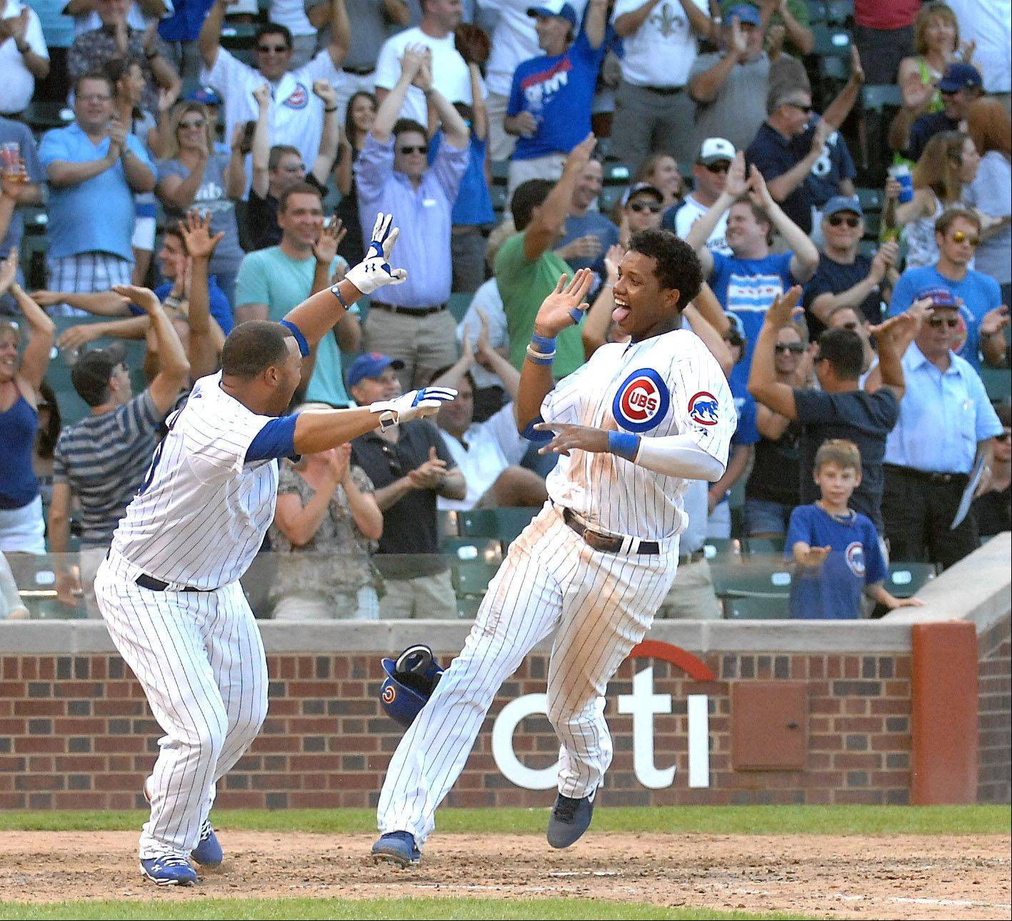 Starlin Castro crosses the plate with the winning run on a hit by Alfonso Soriano to beat Milwaukee 12-11 Thursday at Wrigley Field. At left is Welington Castillo.